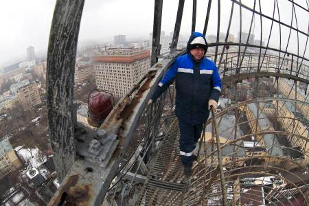 A worker stands on the Shukhov tower's rusted surface.