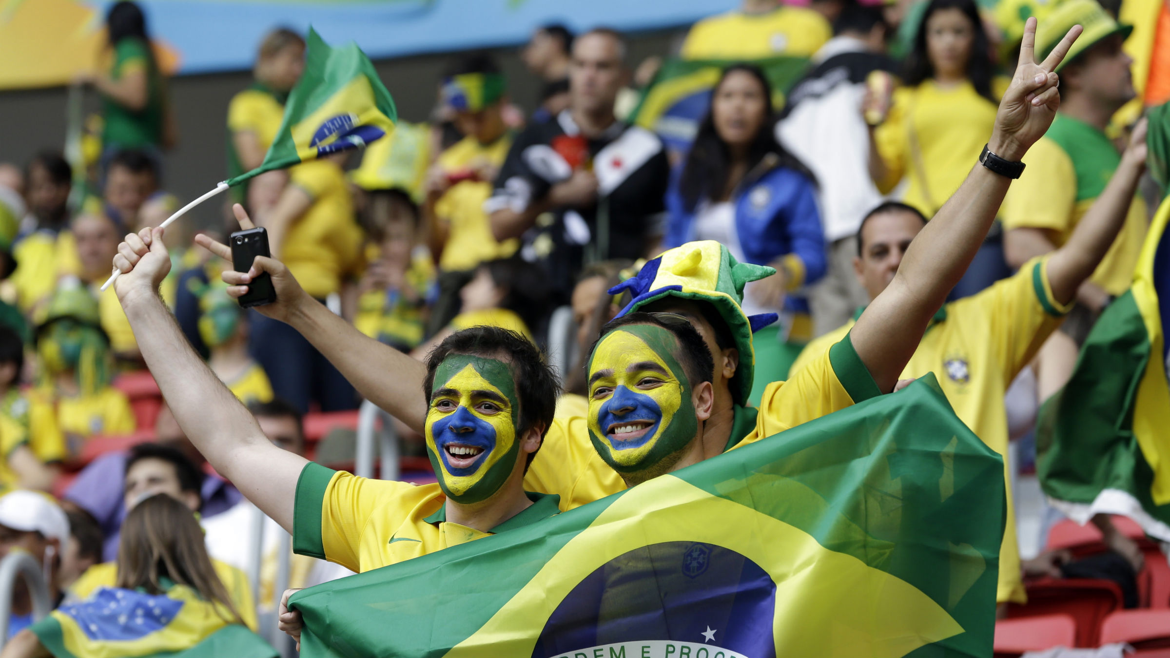 Brazil fans smile prior to the group A World Cup soccer match between Cameroon and Brazil at the Estadio Nacional in Brasilia, Brazil, Monday, June 23, 2014.