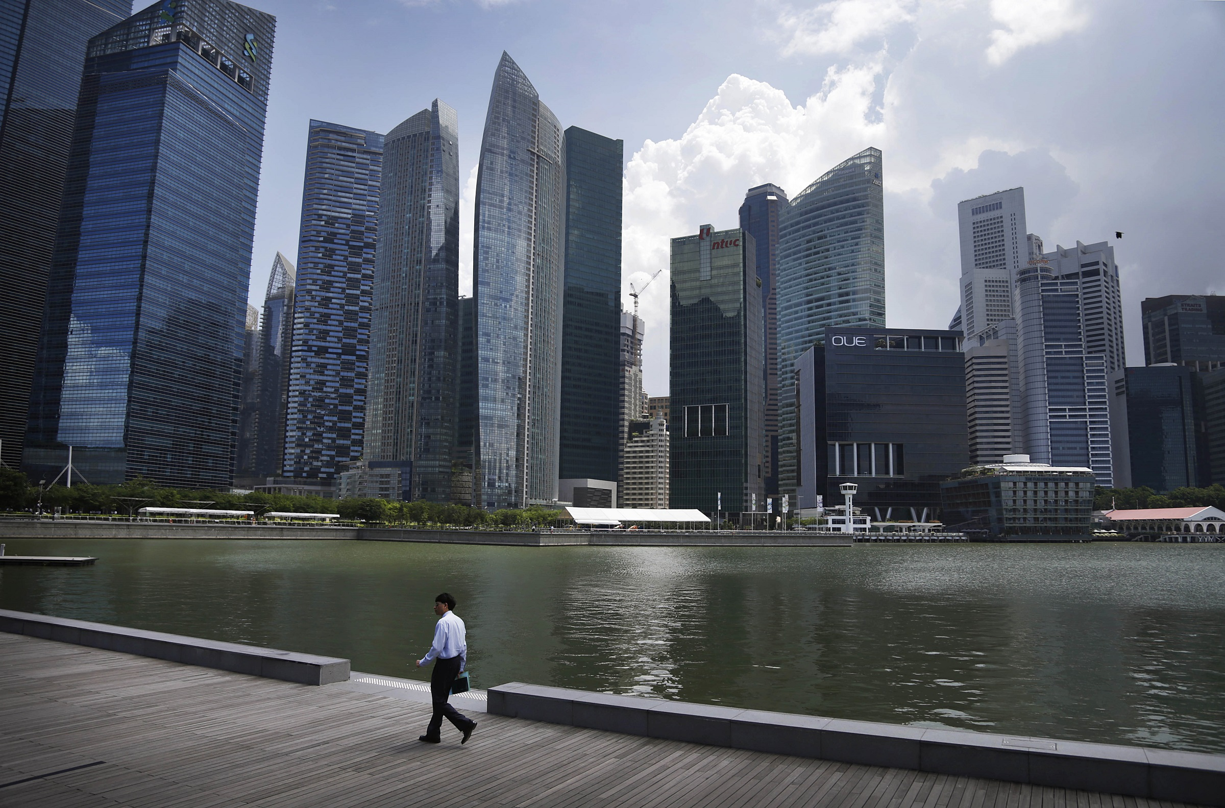 An office worker walks along the Singapore River front during the lunch hour Monday, May 5, 2014 in the central business district of Singapore. (AP Photo/Wong Maye-E)