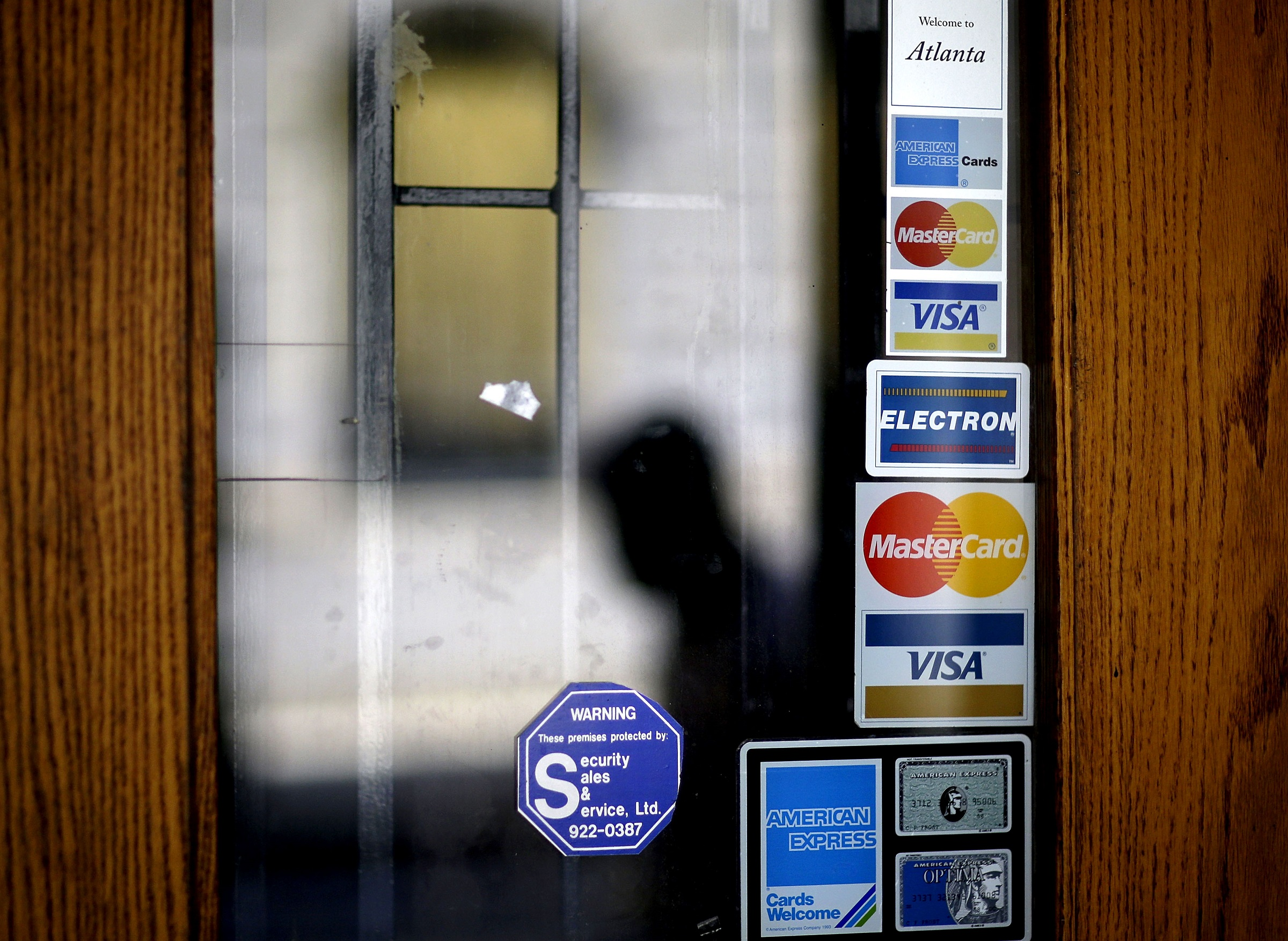 FILE - In this July 18, 2012 file photo, credit card logos are seen on a downtown storefront as a pedestrian passes in Atlanta. Household debt surged at an unprecedented rate in the five years before the financial crisis. In the U.S., the U.K. and France, it soared more than 50 percent per adult. For the world's top 10 economies, it jumped 34 percent. Then the financial crisis hit, and people slammed the brakes on borrowing. Debt per adult in the 10 countries fell 1 percent in the 4½ years after 2007. Economists say debt hasn't fallen in sync like that since the end of World War II.  (AP Photo/David Goldman, File)
