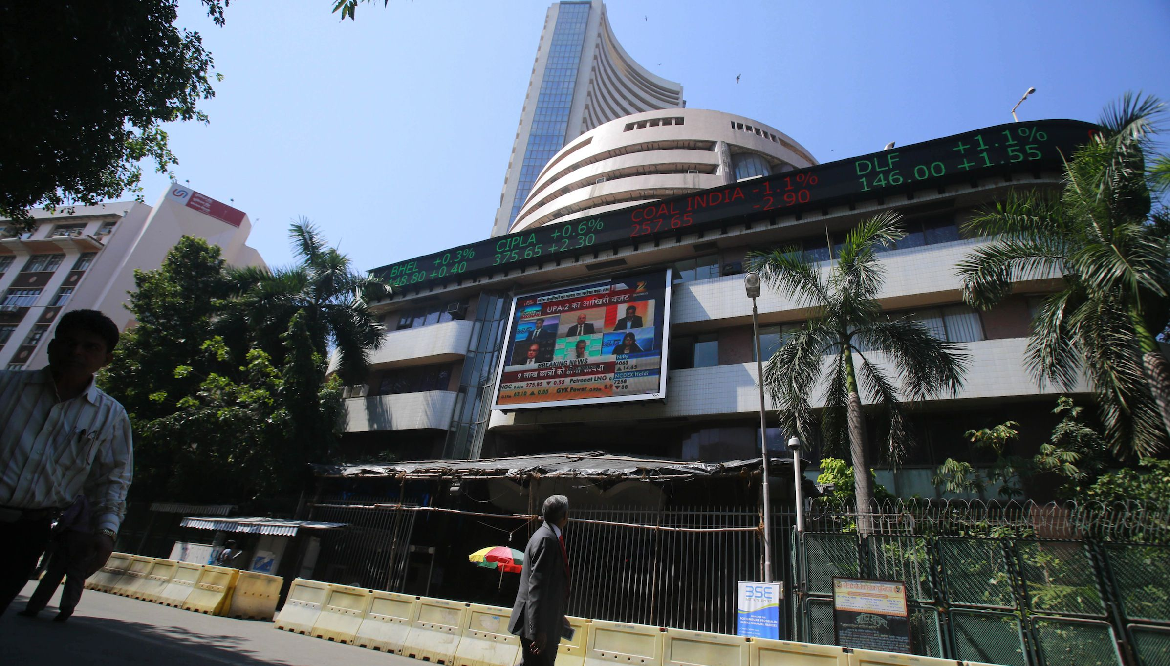 A man watches sensex on a display screen on the facade of the the Bombay Stock Exchange (BSE) building in Mumbai , India, Monday Feb. 17, 2014. India's Finance Minister P. Chidambaram has unveiled a conservative budget for the government's remaining time in office through May in parliament. (AP Photo/Rafiq Maqbool)