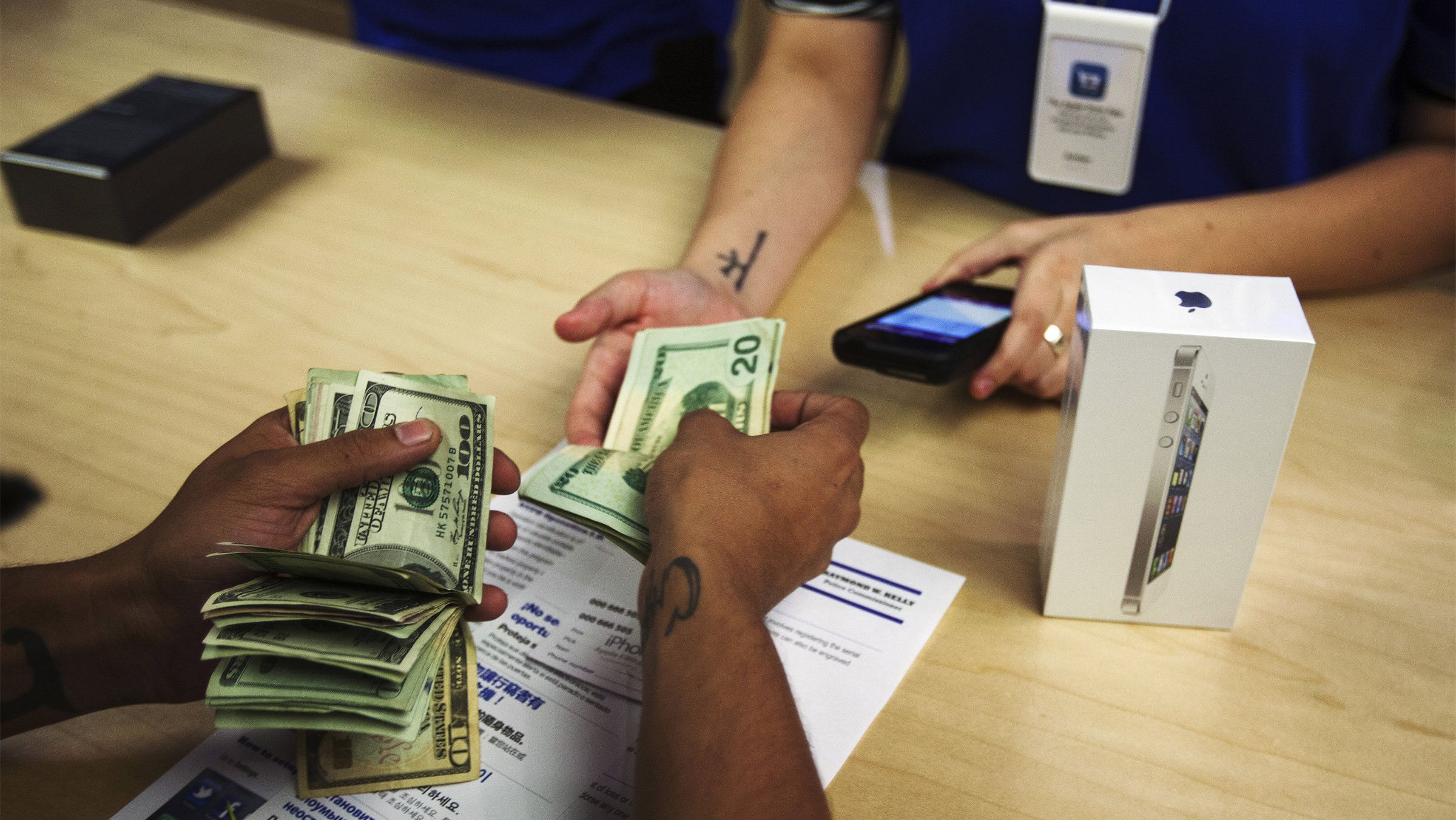 A man pays cash for an Apple iPhone 5 phone in the Apple Store on 5th Avenue in New York, September 21, 2012.