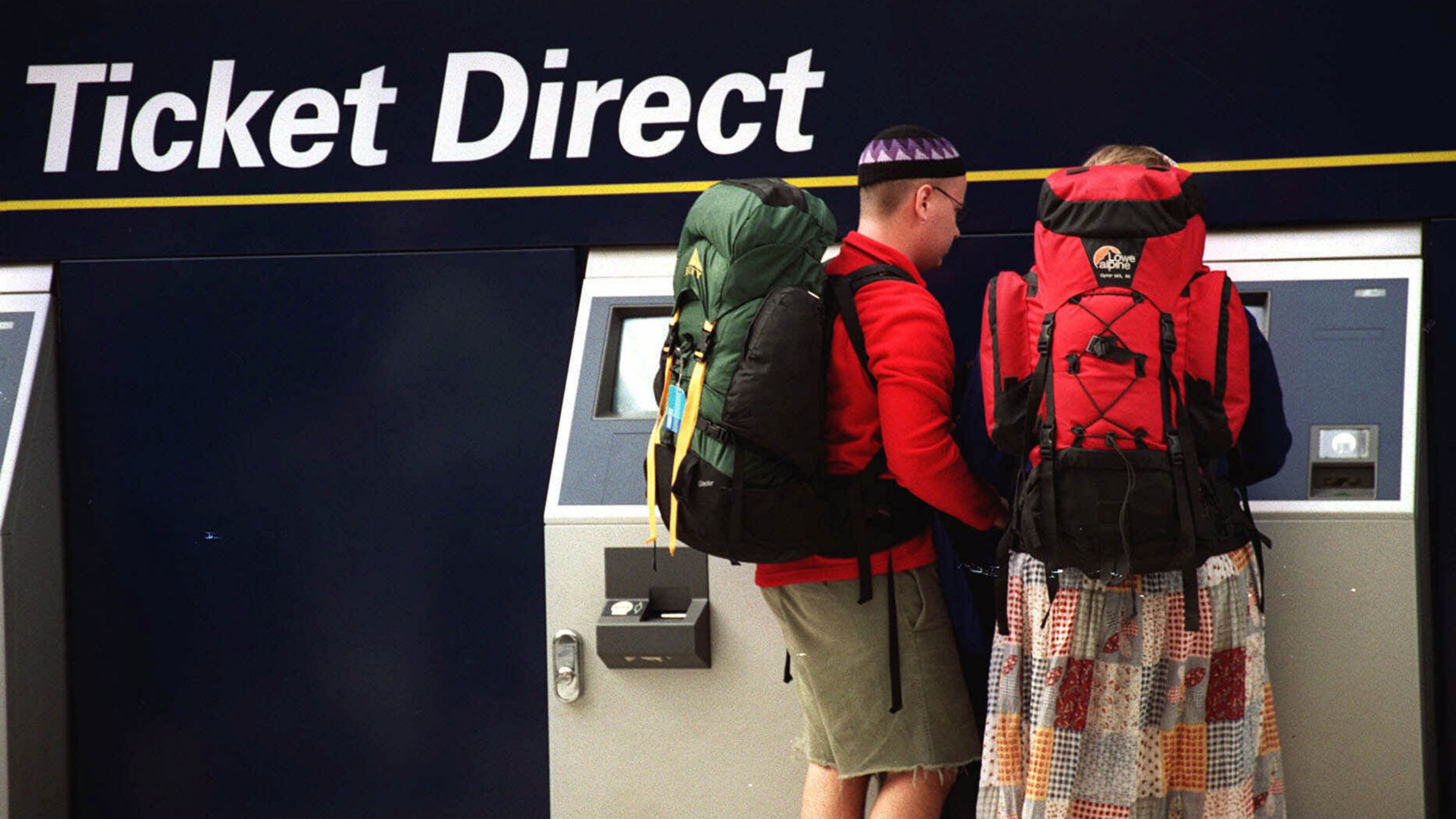Backpackers buying travel tickets