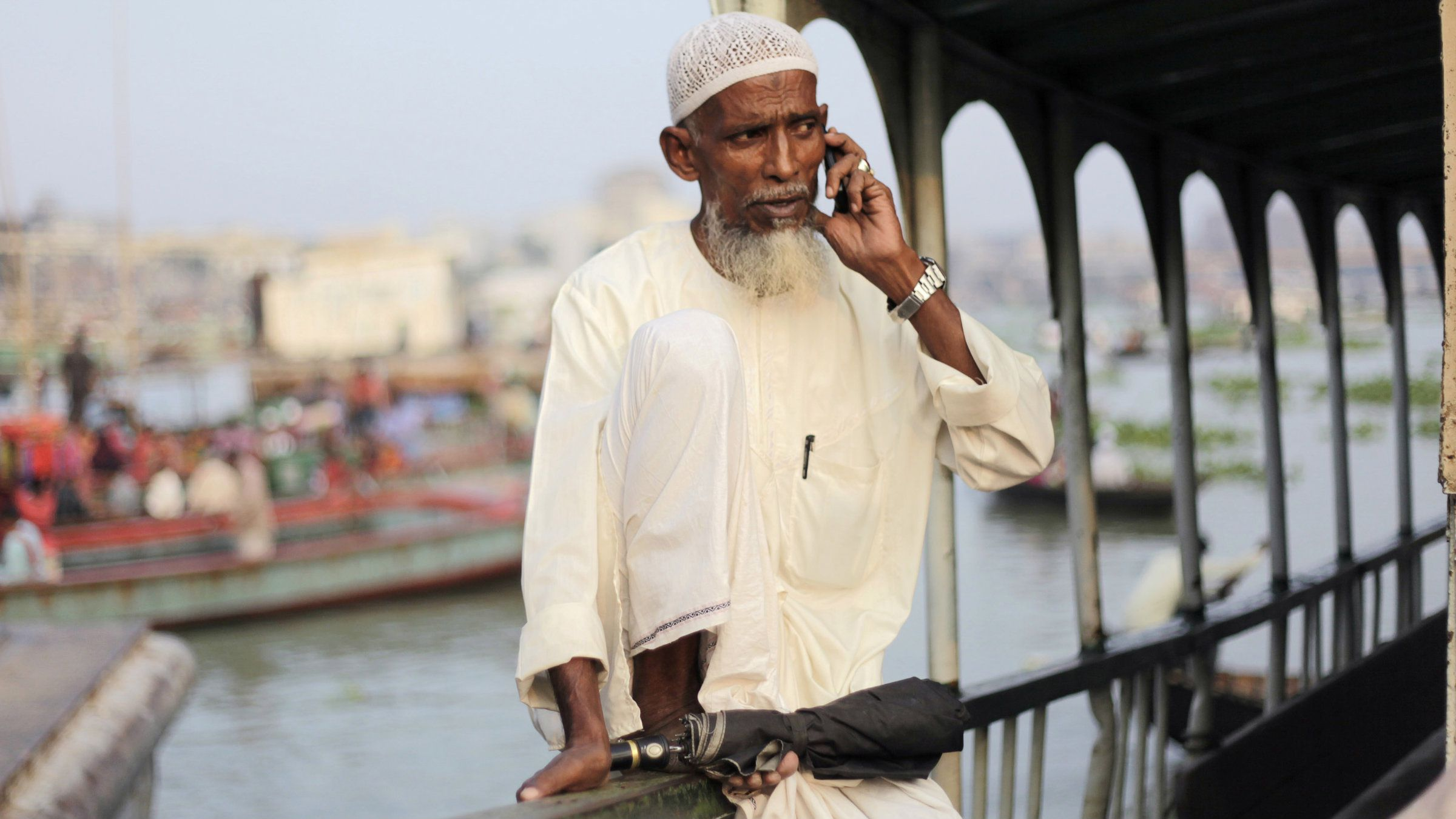 A man talks on the phone as he waits to board a boat by the river Buriganga in Dhaka.