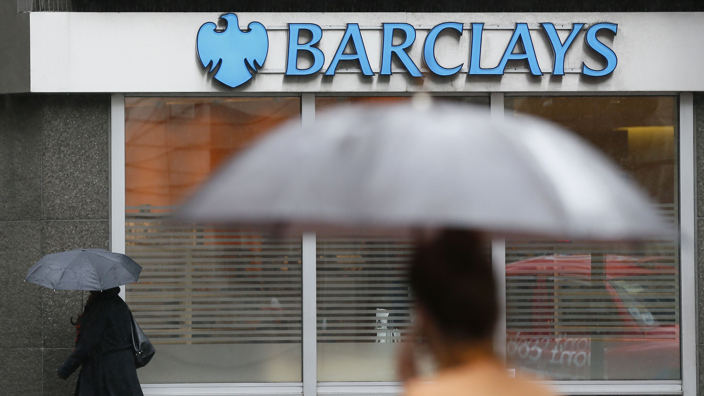 Pedestrians shelter under umbrellas as they walk past a Barclays branch in central London