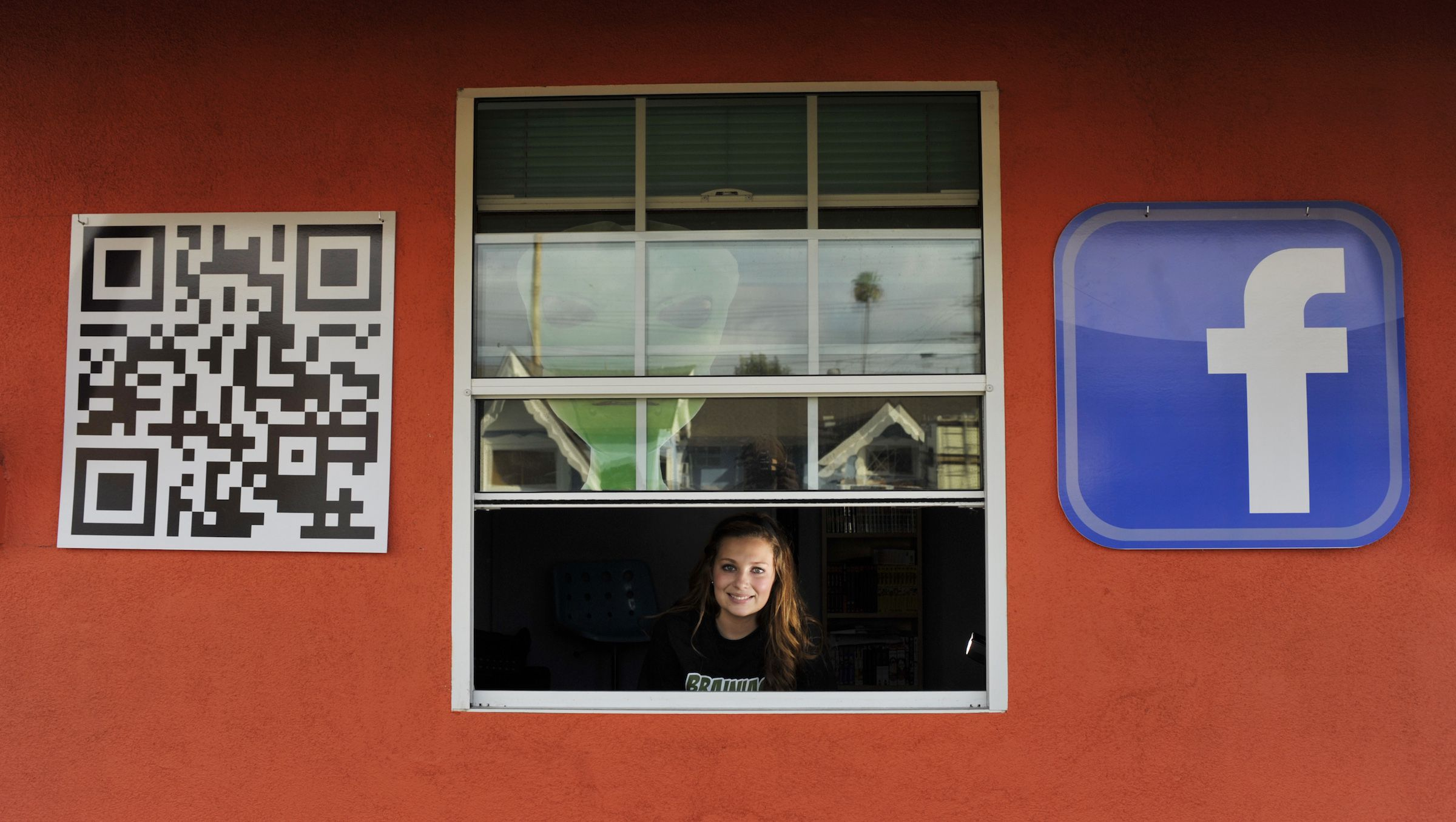 Sarah Hostetler looks out from her home in Buena Park, California February 11, 2012. In return for allowing the front of their four-bedroom house to become a garish advertisement, the Hostetlers are getting their nearly $2,000 monthly mortgage paid by the marketing company behind the project, Brainiacs From Mars.   REUTERS/Josh Edelson (UNITED STATES  - Tags: BUSINESS REAL ESTATE BUSINESS) - RTR2XQQW
