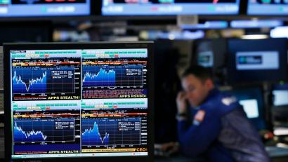 Bloomberg terminal displays news while traders work on the floor of the New York Stock Exchange