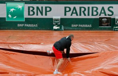 A grounds crew member covers the clay court from rain near the logo of BNP Paribas during the French Open tennis tournament