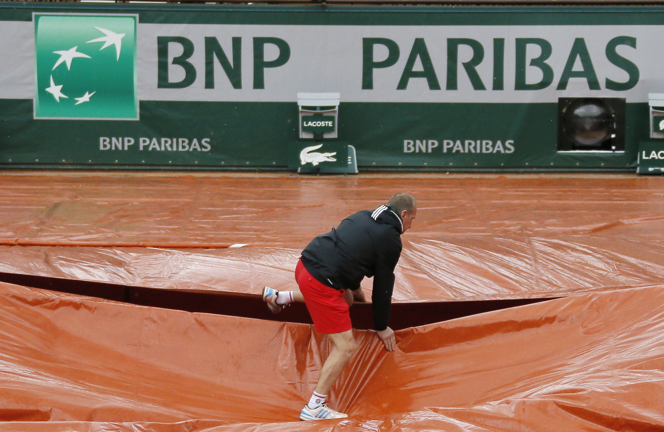 A grounds crew member covers the clay court from rain near the logo of BNP Paribas during the French Open tennis tournament at Roland Garros in Paris May 30, 2014. Shares in France's biggest bank BNP Paribas fell sharply on Friday on concerns a possible fine for alleged sanctions after a report in the Wall Street Journal said the U.S. Justice Department wanted $10 billion from the bank - double the amount which had been previously reported.   REUTERS/Gonzalo Fuentes (FRANCE - Tags: BUSINESS SPORT TENNIS LOGO) - RTR3RK3L