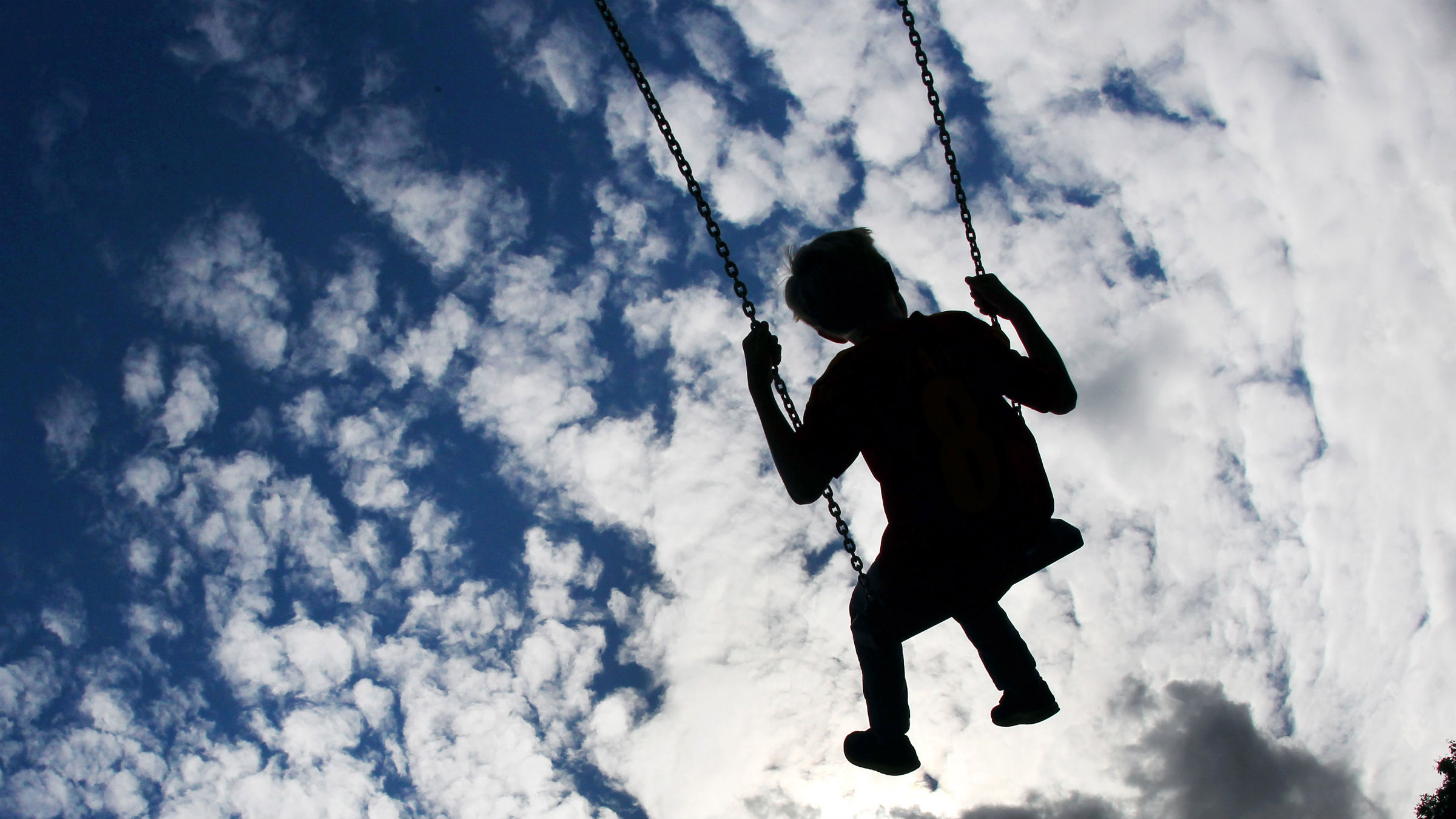 A child seen on swings under a blue sky with clouds on a playground in Frankfurt, Germany, Thursday, July 12, 2012. Sun, rain, wind and cold temperatures are forecasted for the next days all over Germany.