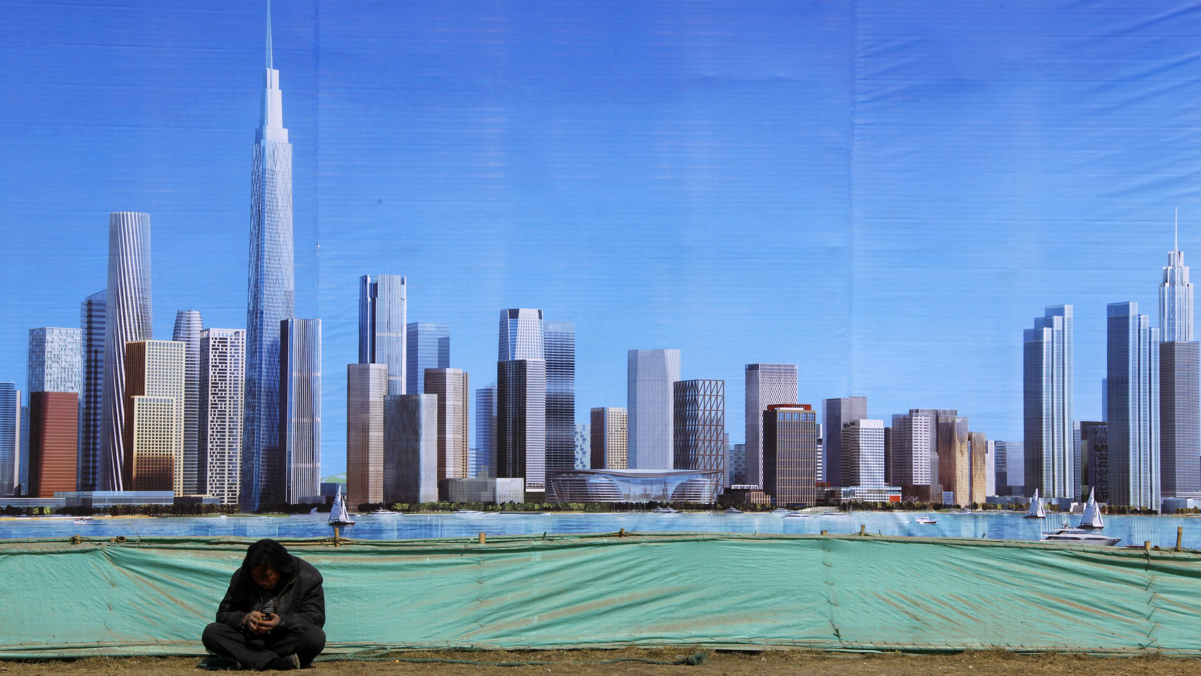A worker rests in front of a billboard displaying an artist's impression of the new business district of Binhai, located in the Yujiapu financial zone on the outskirts of the city of Tianjin March 2, 2011. Round-the-clock construction is transforming muddy ground into what officials boast will be the world?s largest financial zone, a monument to the ambitions that have driven China to dizzyingly fast growth. When the country?s leaders gather for their annual parliament in Beijing on Saturday, they will endorse plans to tap the brakes on the speeding economy, a shift that is needed to keep inflation and debt, under control for now, from becoming far more troublesome. But they need only make the one-hour trip to the financial district sprouting up in Tianjin to see how hard-driving local officials, cash-rich state-owned banks and the soaring aspirations of people seeking a better life are imperiling their designs for slower, steadier growth. REUTERS/David Gray
