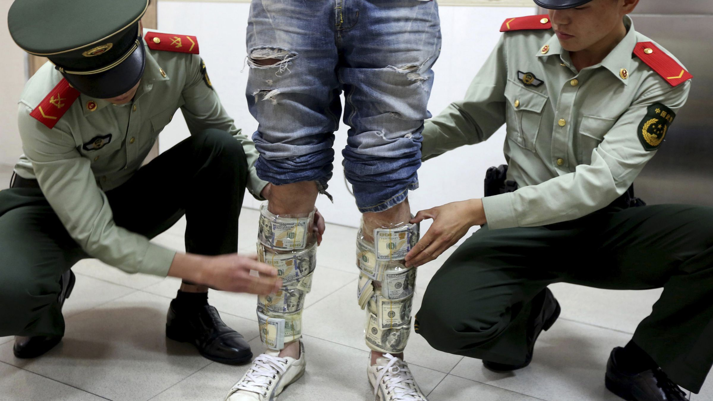 china dollar debt Paramilitary policemen take off U.S. dollars strapped around a man's legs, at the border of Hong Kong and Shenzhen, Guangdong province, April 24, 2014. According to local media, the man was found trying to smuggle in total US$580,000 from the mainland to Hong Kong. Picture taken April 24, 2014. REUTERS/China Daily