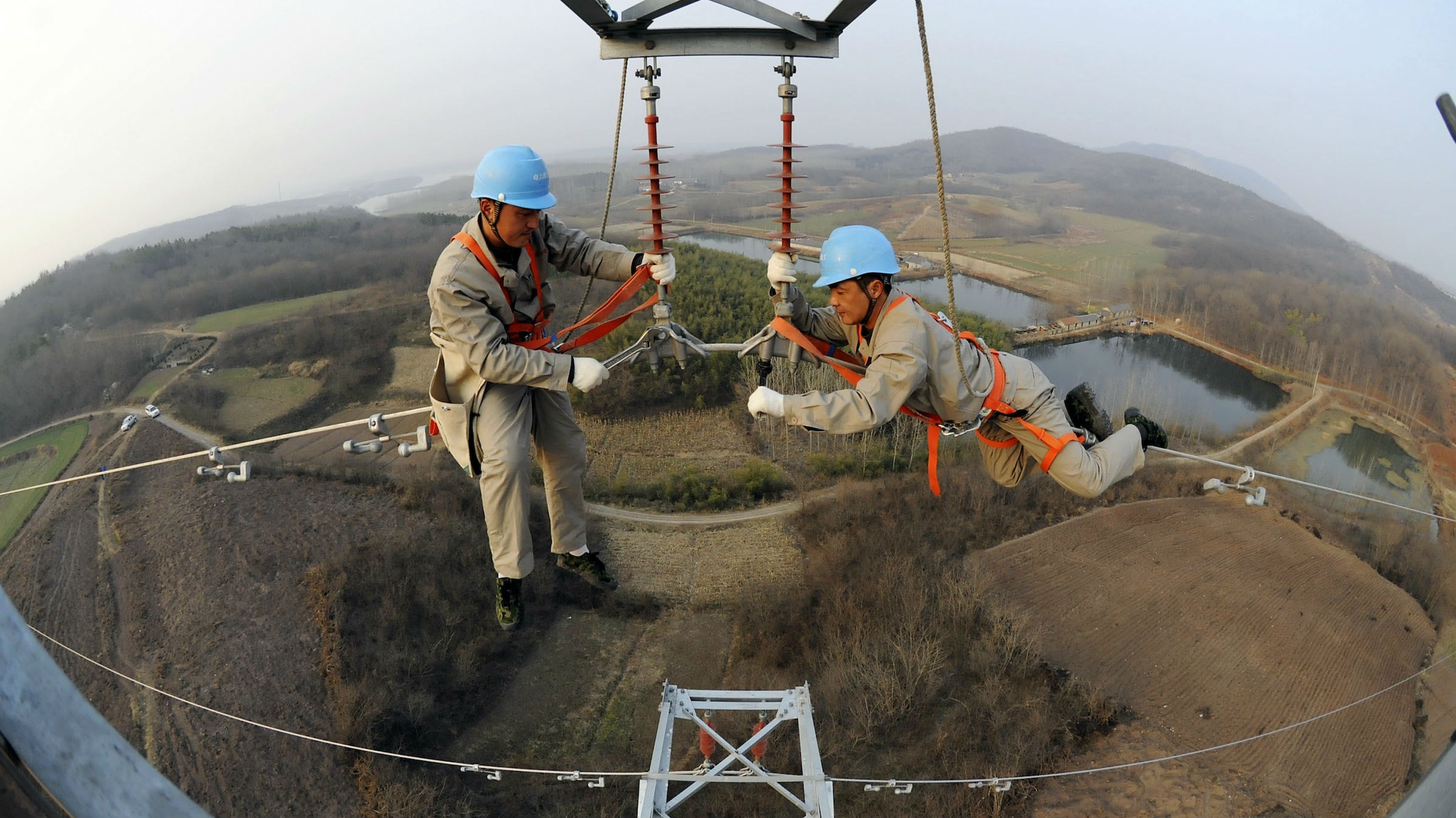 Workers check on electricity pylon situated amid farmlands in Chuzhou, Anhui province.
