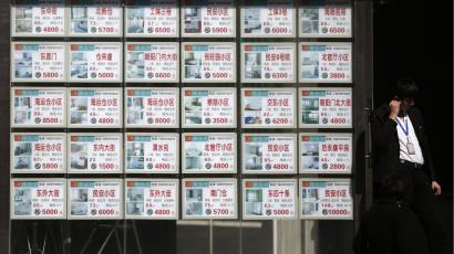 A man stands next to a board advertising apartments for sale or rental at a real estate agency in Beijing February 27, 2014. China's major lenders have not tightened or halted their property-related lending business, the official Xinhua news agency said, after local media reported that some banks had stopped lending to real estate developers. china housing property evergrande longfor greenland slump mortgage REUTERS/Kim Kyung-Hoon