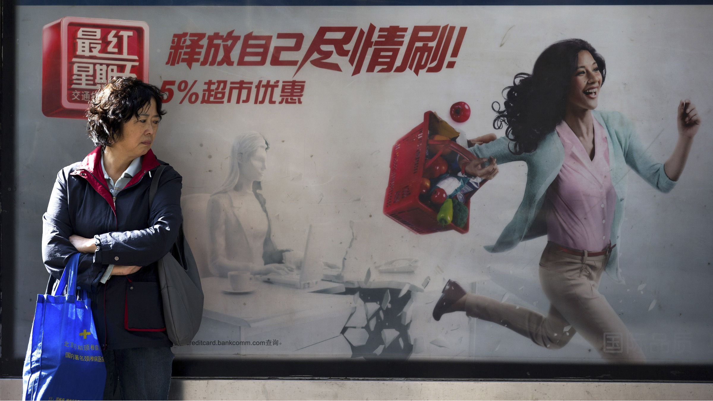 """China economy consumption consumer slowdown housing market savings A Chinese woman waits at a bus stand with a billboard advertised a bank's credit card promotion with words """"Release yourself, swap it as much as you can"""" in Beijing Thursday, Oct. 18, 2012. China's worst slump since the global financial crisis leveled out in the latest quarter and retail sales picked up in a sign an economic rebound is taking shape, adding to hopes for a global recovery. (AP Photo/Andy Wong"""