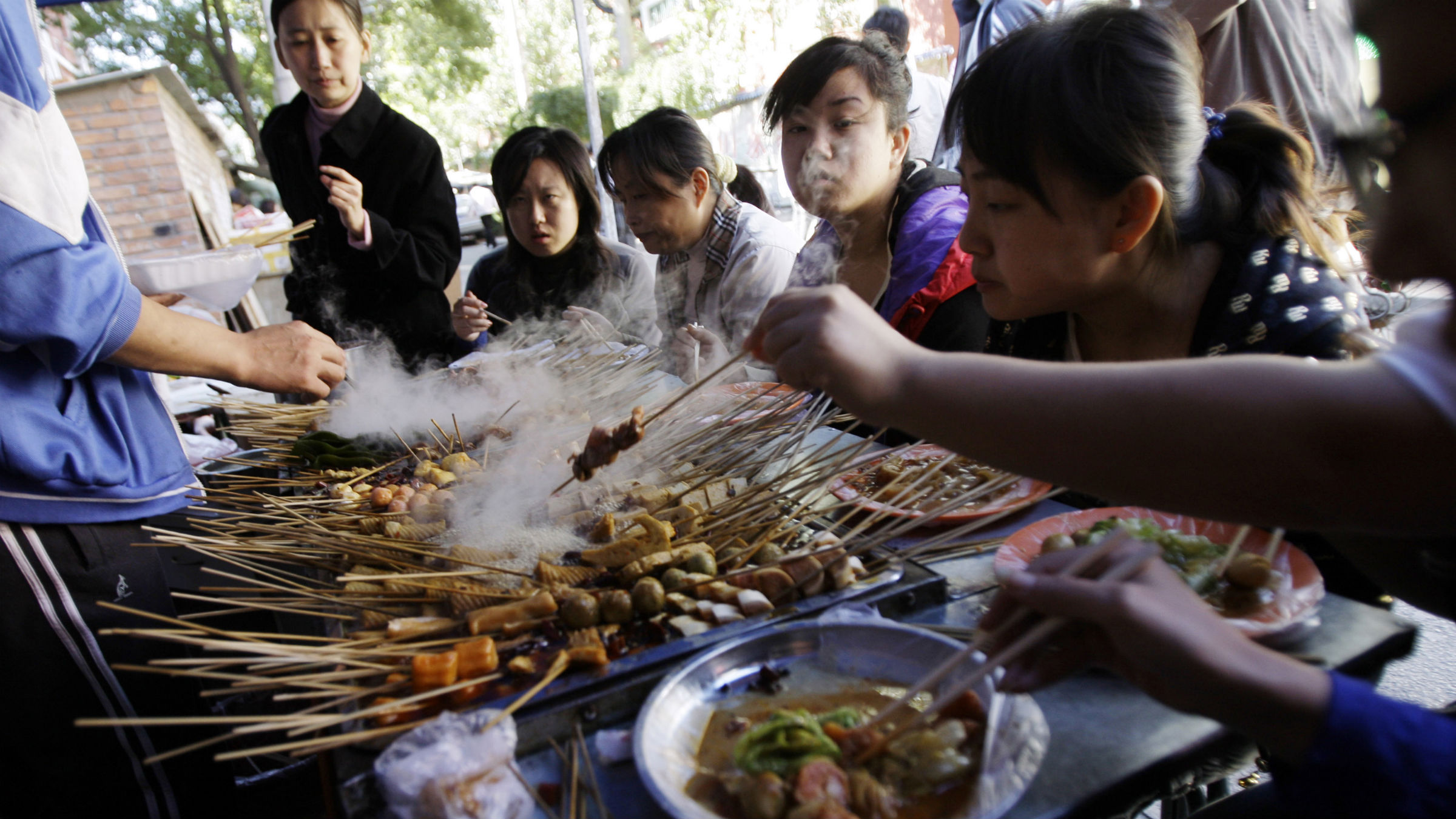 Customers eat at a food stall in a street in Beijing Wednesday, Oct. 8, 2008. Many food stalls have reopened on Beijing streets after being closed down during the Olympic Games.