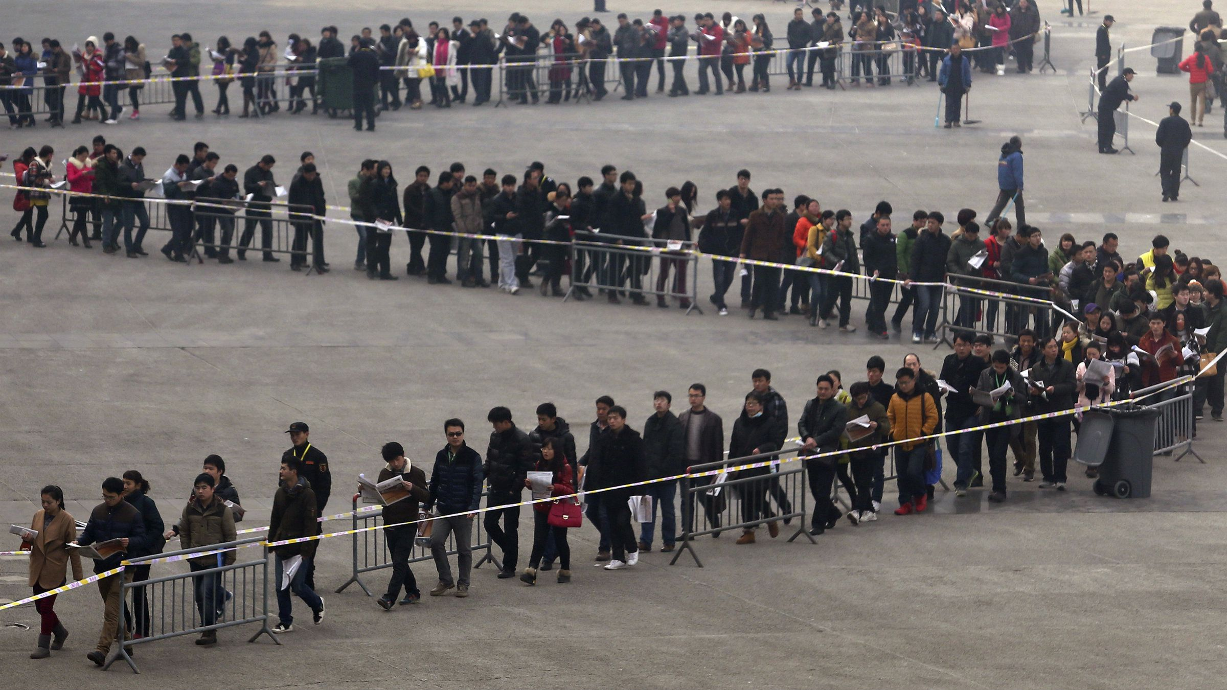 Junior college students line up outside a job fair in Zhengzhou, Henan province