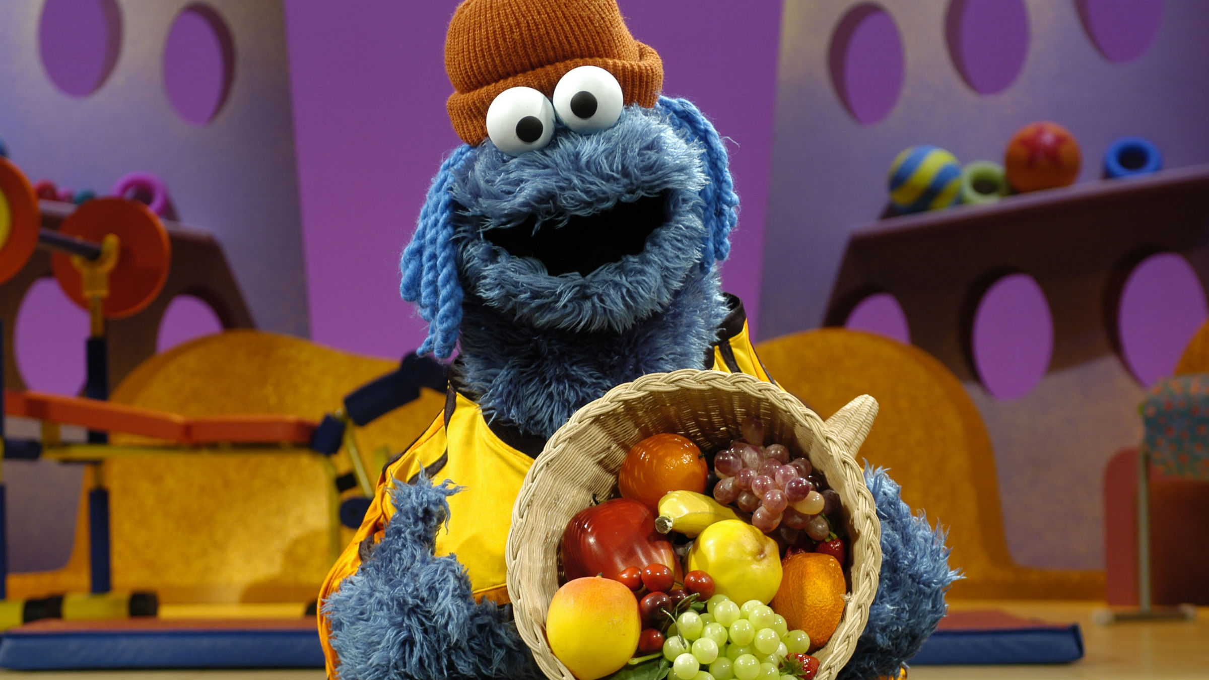 Cookie Monster holding a basket of vegetables and fruit
