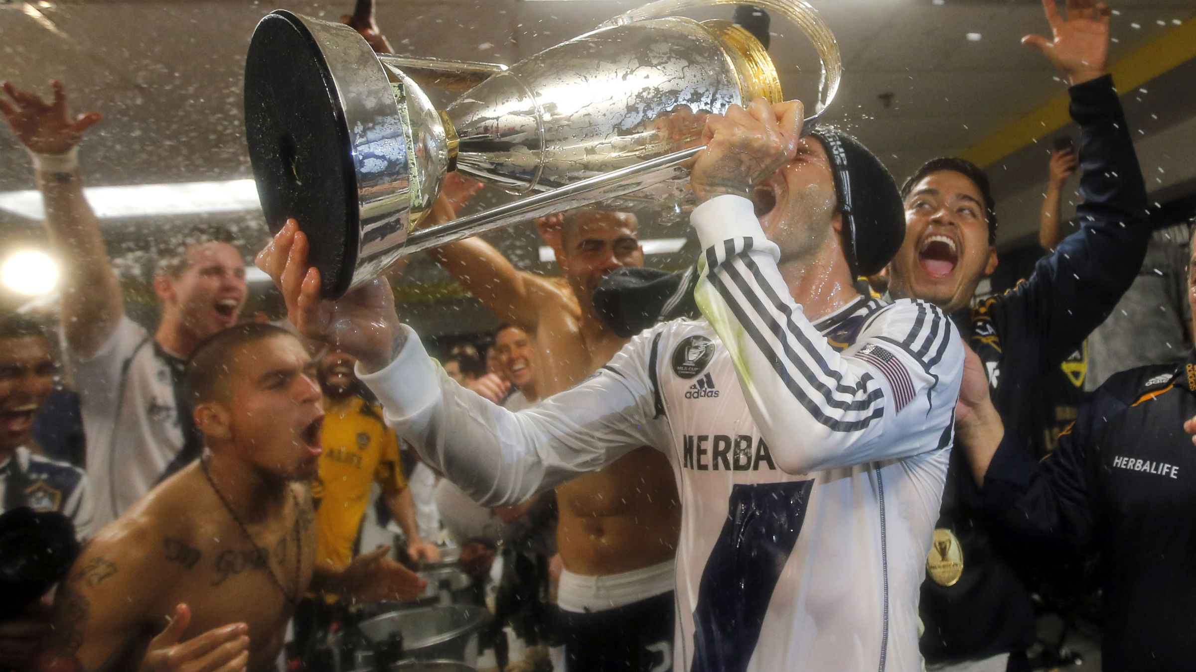 David Beckham celebrating in a locker room, drinking champagne out of a trophy.