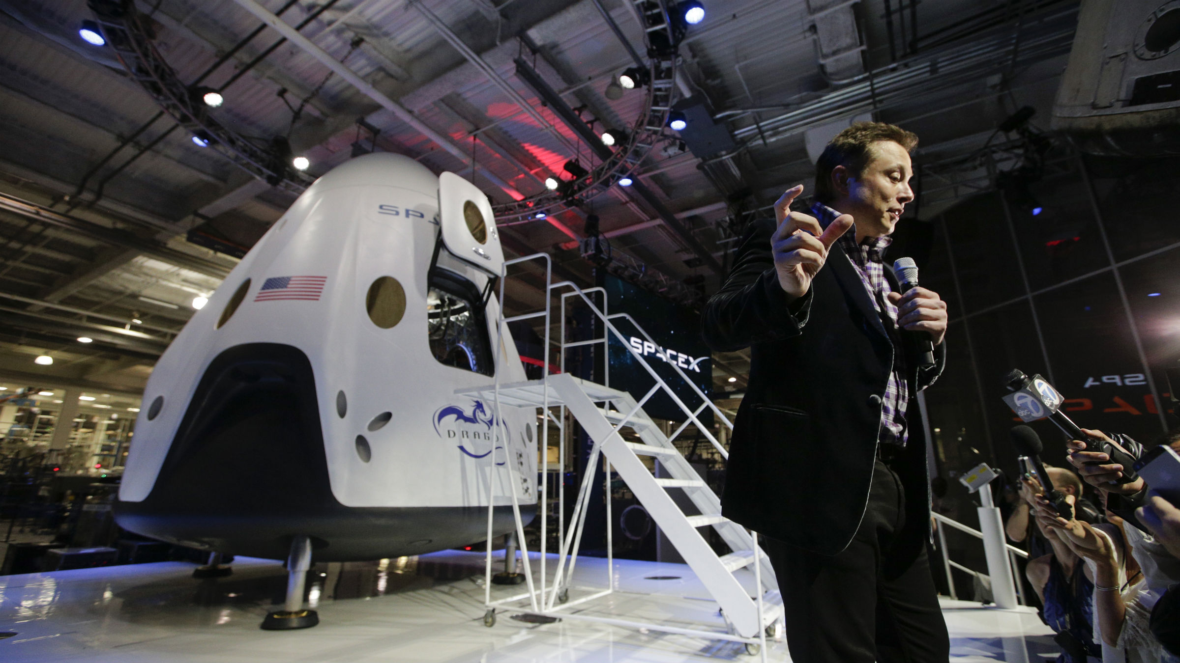 Elon Musk, CEO and CTO of SpaceX, answers questions from the media in front of the SpaceX Dragon V2 spaceship at the headquarters on Thursday, May 29, 2014, in Hawthorne, Calif. SpaceX, which has flown unmanned cargo capsules to the International Space Station, unveiled the new spacecraft Thursday designed to ferry astronauts to low-Earth orbit.