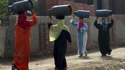 Women carrying gas cylinders to and from the market in Cairo.