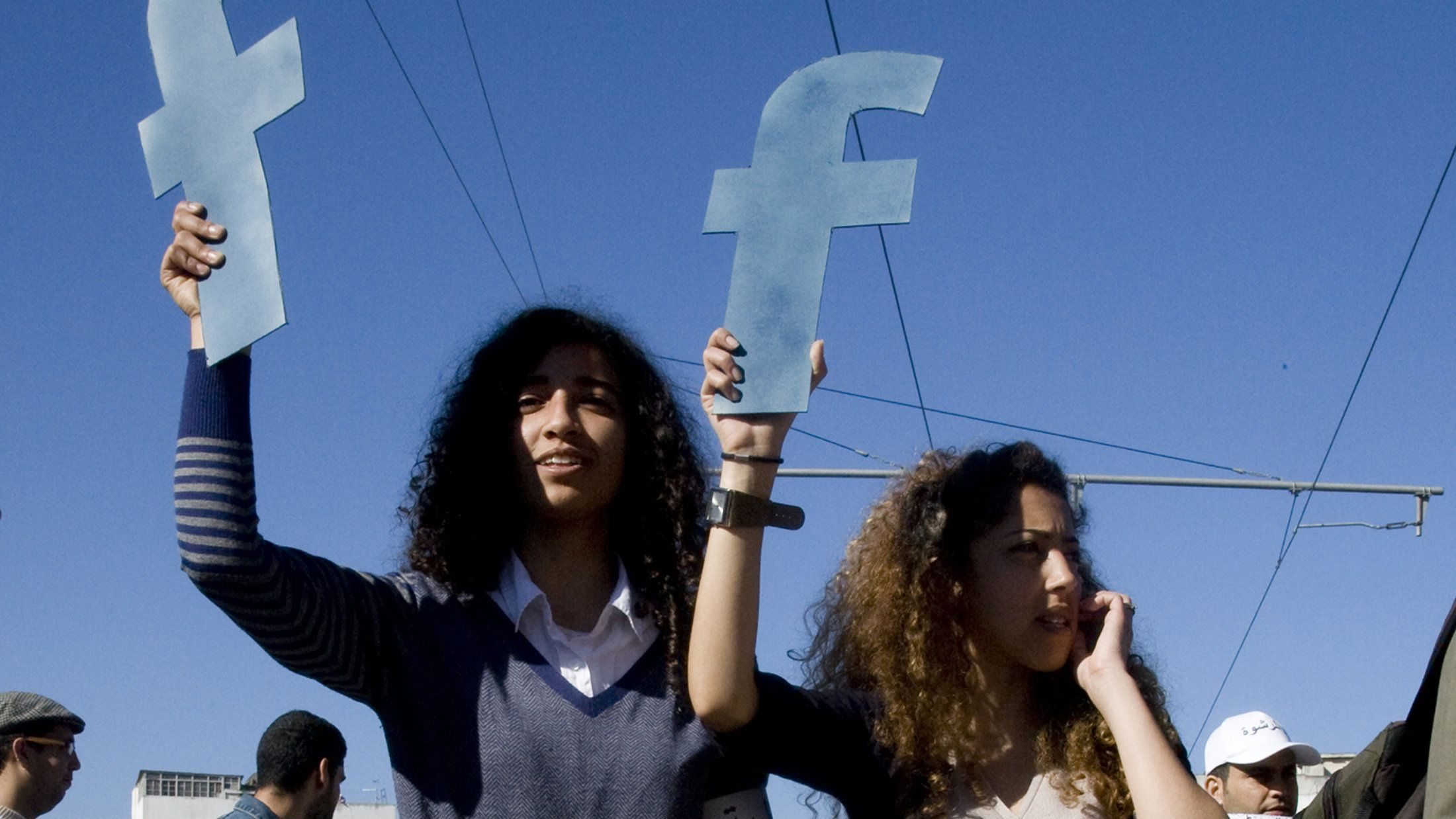 """Protesters hold """"f""""s in recognition of social network site Facebook's role in the North African revolts, during a protest in Rabat."""