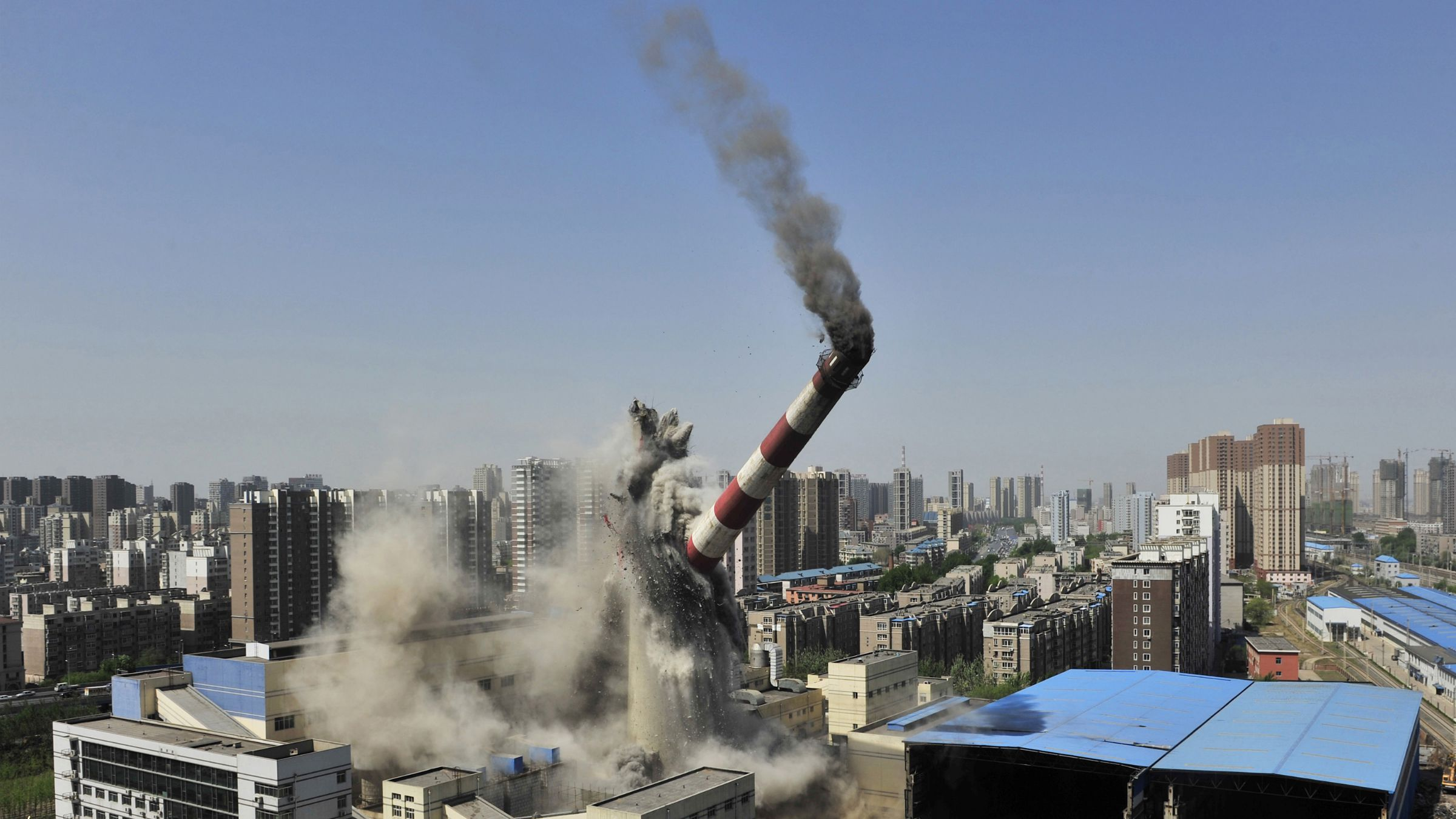 The provincial highest chimney collapses as it is demolished by explosives in Shenyang, Liaoning province, April 28, 2014. The 150-metre-high chimney used to be part of a local heating factory, according to local media. china fiscal stimulus spending real estate property housing collapse