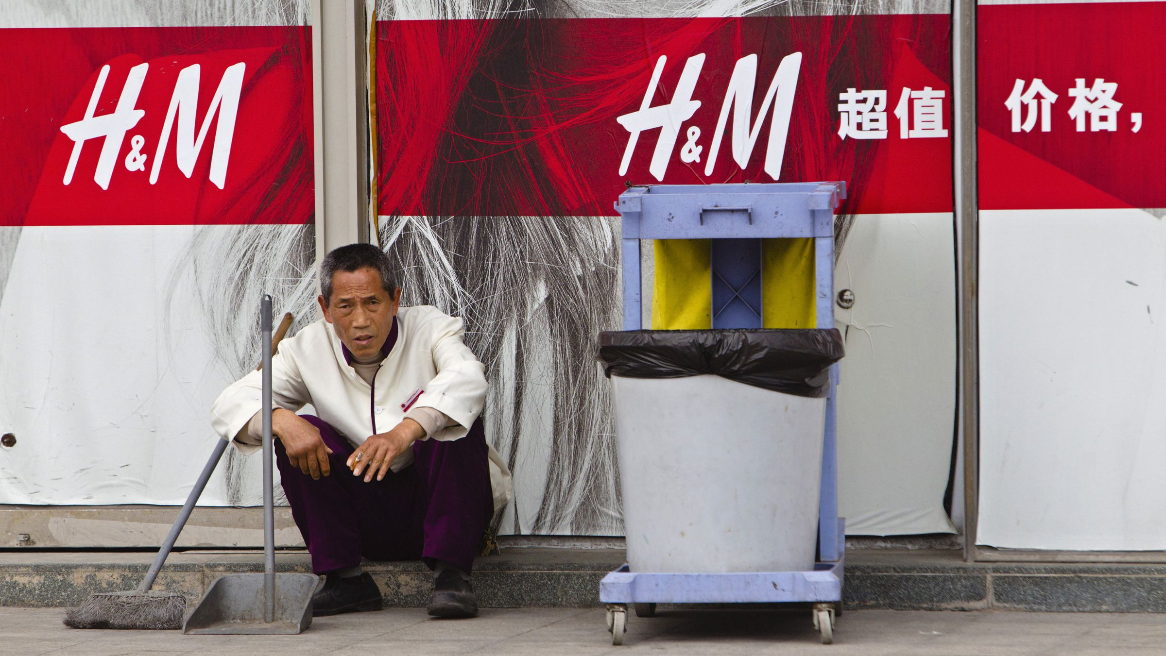 A cleaner sits in front of an H&M store in Guangzhou, China