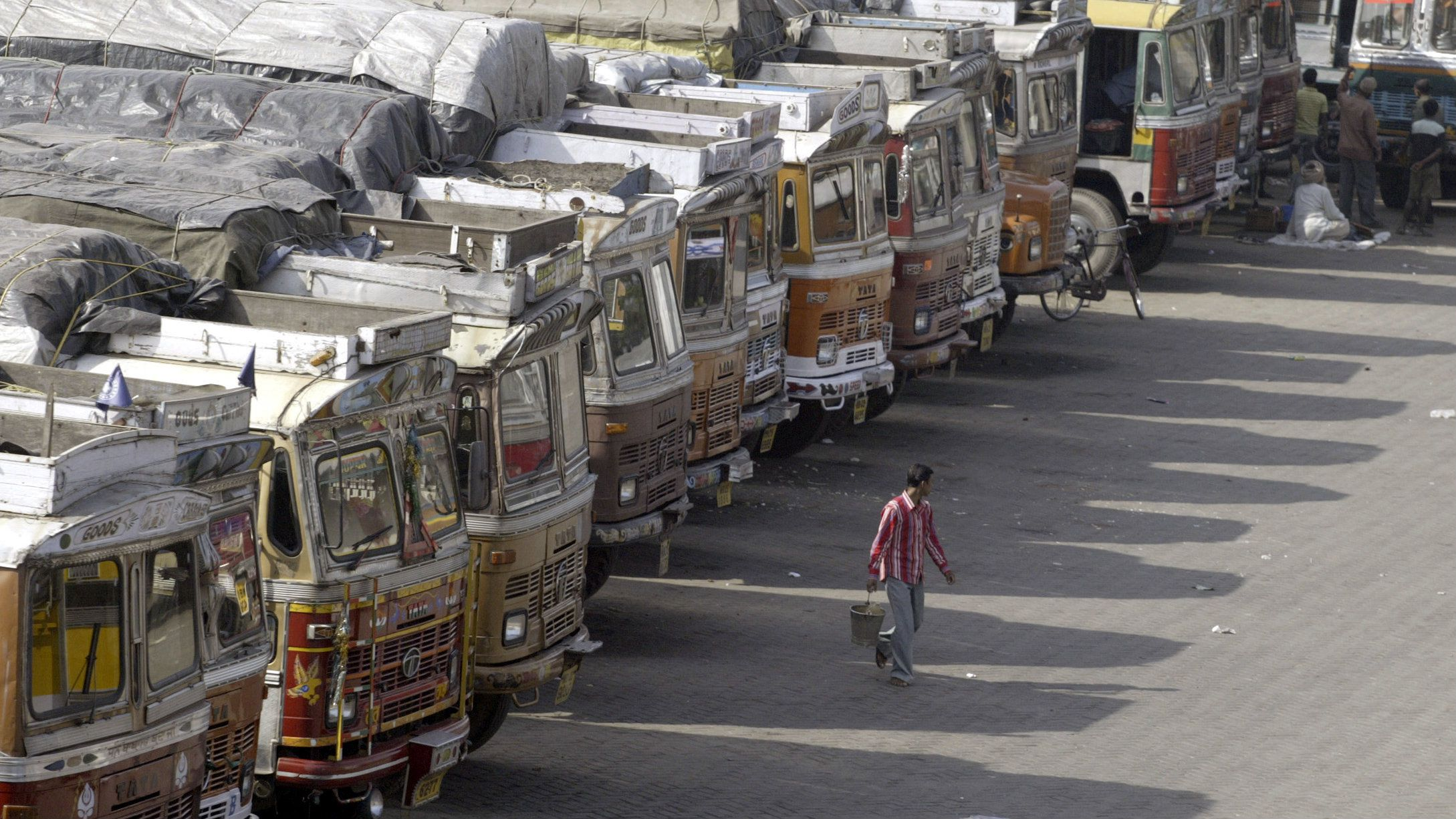 A man walks in a truck terminal near the India-Bangladesh border in Petrapole, about 80 km (49 miles) northwest from the eastern Indian city of Kolkata November 16, 2006. Thousands of trucks and people from both countries were stranded for the last four days due to political unrest in Bangladesh, local media reported. REUTERS/Parth Sanyal (INDIA)