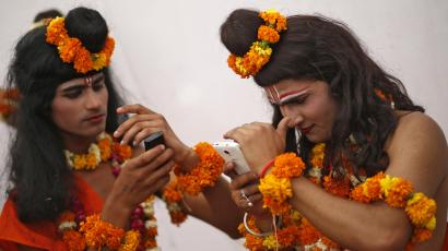 Two men dressed as Indian religious figures check their mobile phones.