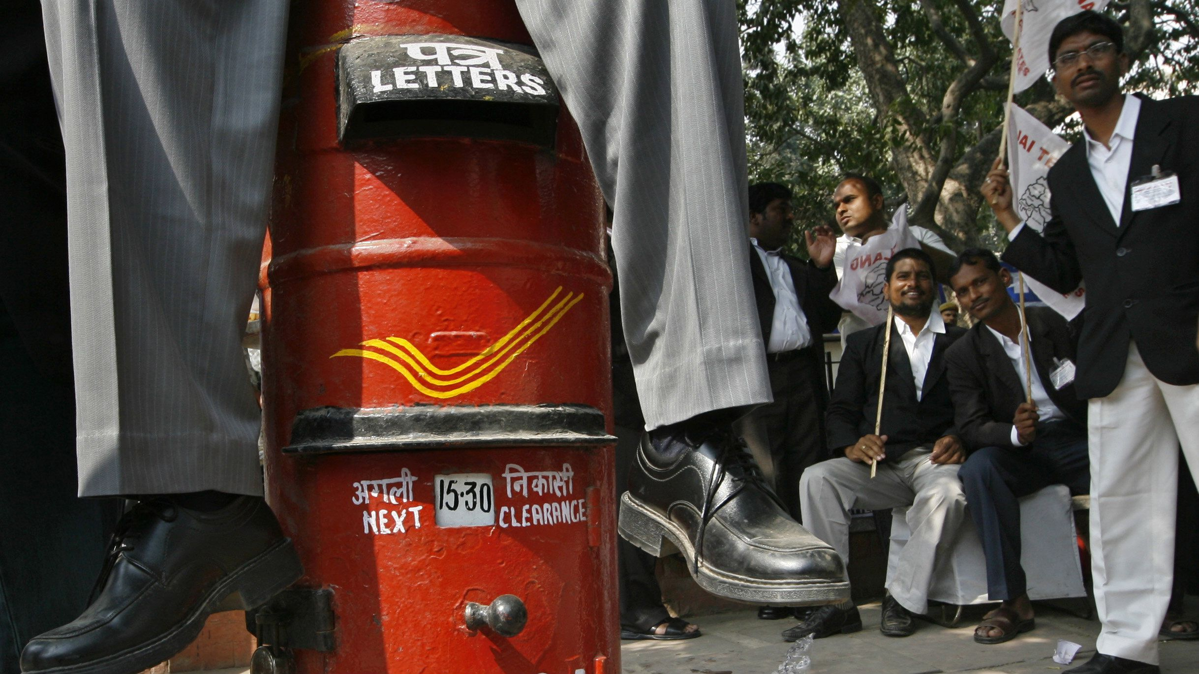 A pro-Telangana supporter sits on a letter box as others watch during a protest in New Delhi February 22, 2010. The protest was held to demand a new state to be carved in the southern Indian state of Andhra Pradesh, supporters said.  (INDIA - Tags: CIVIL UNREST)