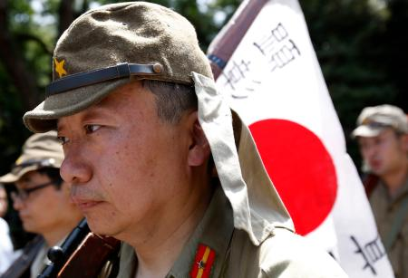 Men dressed as Japanese imperial army soldiers march in front of the gate of the Yasukuni Shrine in Tokyo August 15, 2014, to mark the 69th anniversary of Japan's surrender in World War Two.