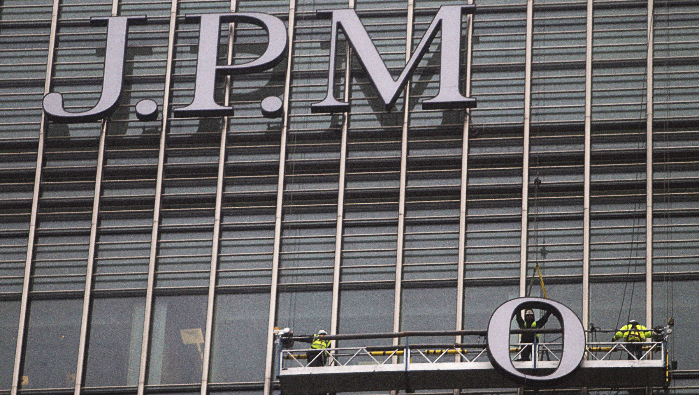 Workers erect a sign for JPMorgan investment bank at Canary Wharf in London