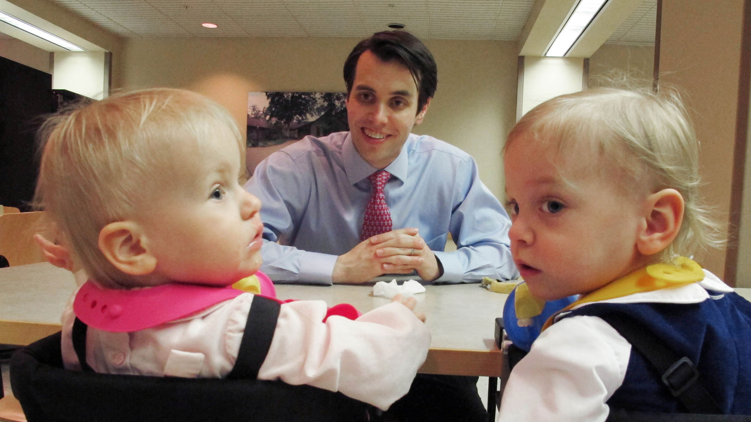Man looks expectantly at twin babies at table