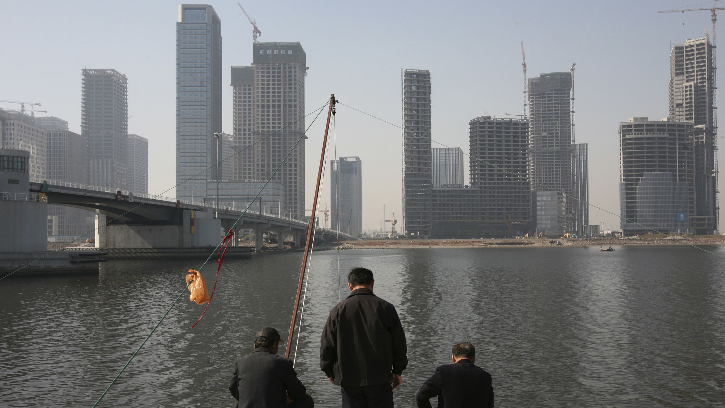 manhattan china tianjing debt ghost town Residents fish with nets on the banks of the Hai River in Tianjin's Binhai New Area, where the government is building its Yujiapu financial center October 23, 2012. The towers in Tianjin's Yujiapu Financial District, and two dozen others on the opposite side of the river, are monuments to the transformation of this once-rundown northern city of 13 million into the country's fastest growing region last year. Picture taken October 23, 2012. REUTERS/Michael Martina