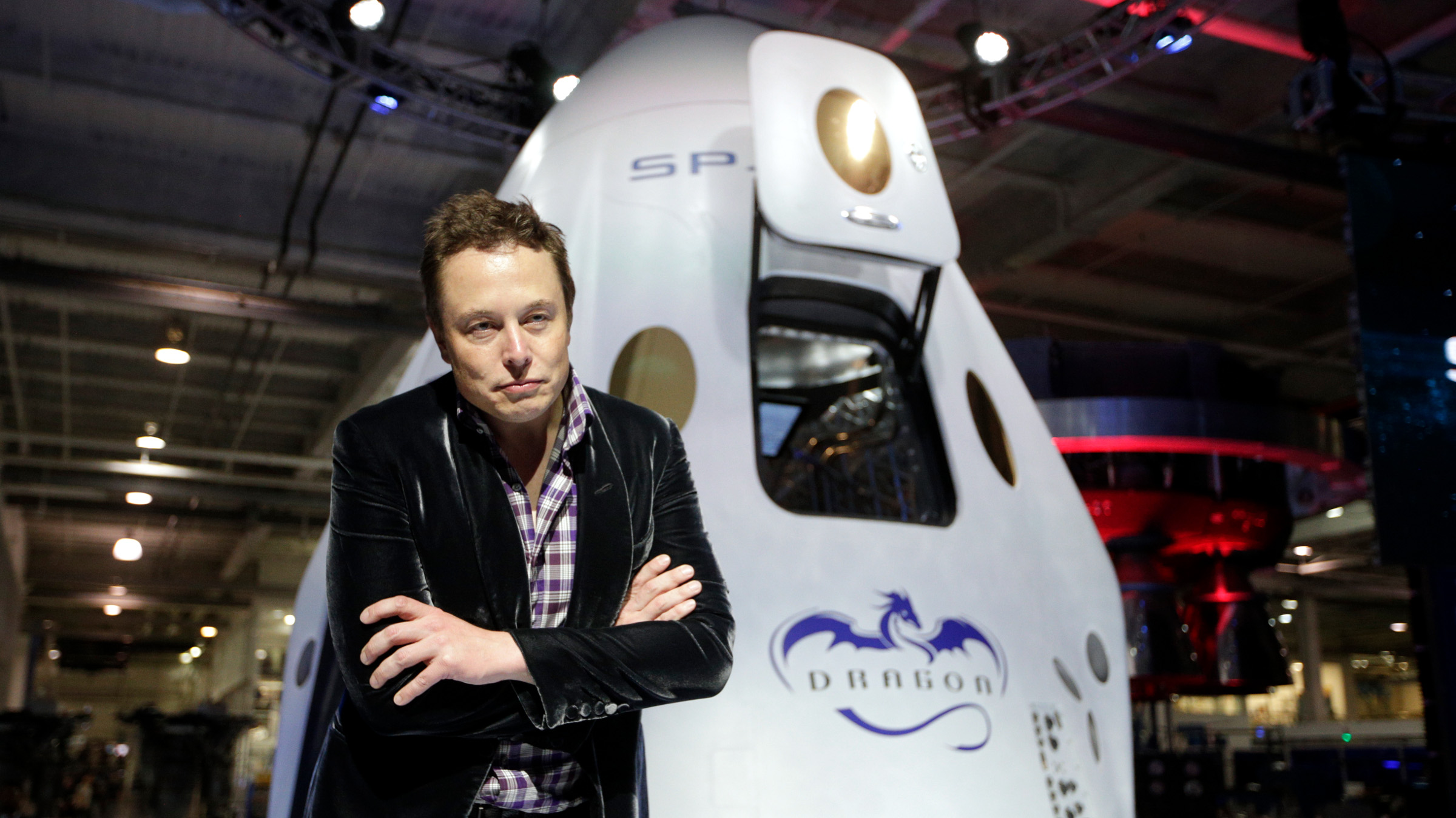 Elon Musk, CEO and CTO of SpaceX, listens to a question from the media in front of the SpaceX Dragon V2 spaceship at the headquarters on Thursday, May 29, 2014, in Hawthorne, Calif. SpaceX, which has flown unmanned cargo capsules to the International Space Station, unveiled the new spacecraft Thursday designed to ferry astronauts to low-Earth orbit. )