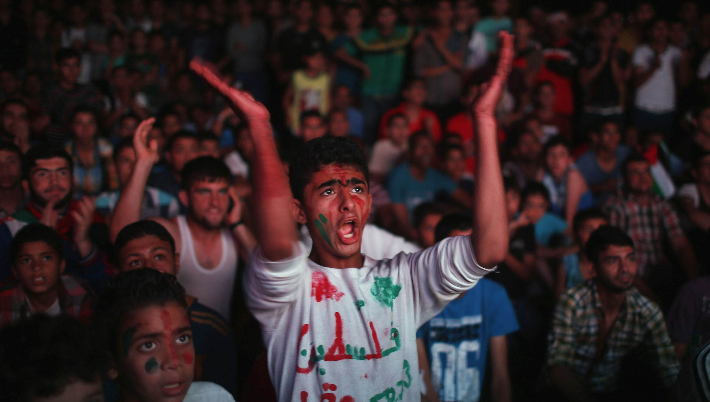 Palestinians cheer as they watch the soccer match between their national team and Philippines on large screens during the AFC Cup Final, in Gaza City May 30, 2014, REUTERS/Mohammed Salem (GAZA - Tags: SPORT SOCIETY SOCCER TPX IMAGES OF THE DAY) - RTR3RKGA