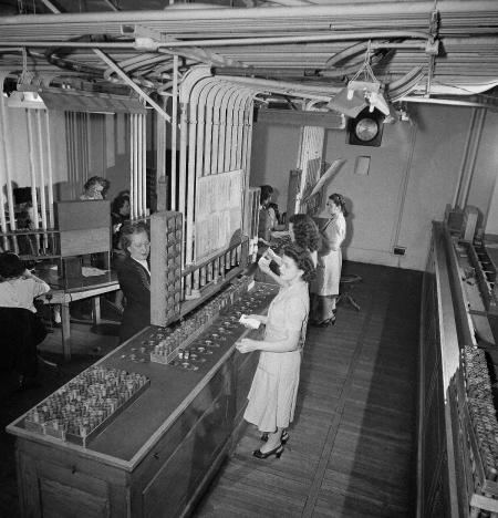 Over six miles of pneumatic tubes carry messages in the Curb Exchange's ultra-modern system of communications in New York City, Sept. 6, 1947. In this portion of the tube room clerks are -routing buy and sell orders from telephone clerks to the individual trading posts. Orders requiring prompt action are signaled or handed by the clerks on the floor to the brokers. Orders not so urgent other communications are handled through the tube system. ()