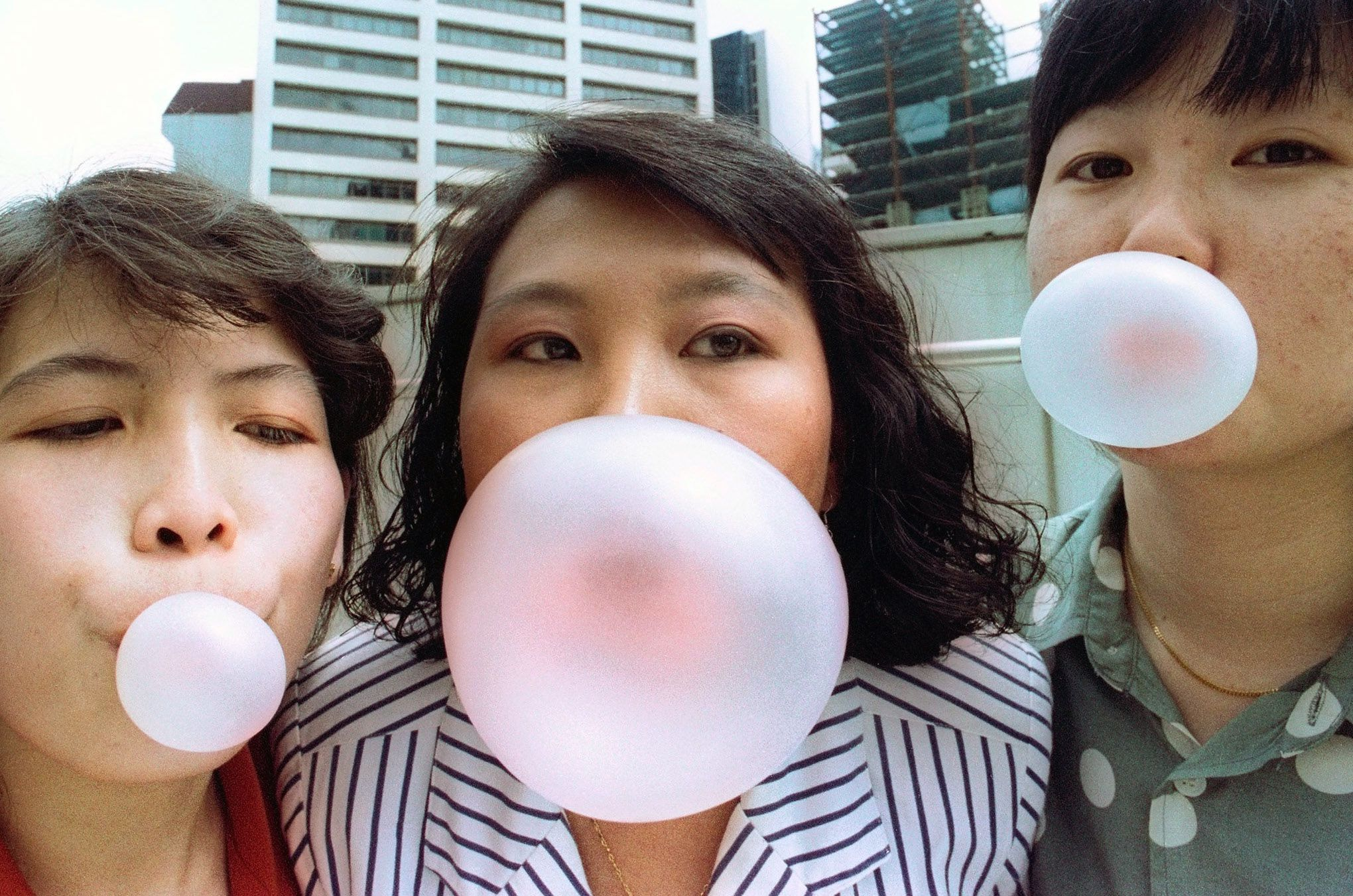 Singaporeans pose while blowing bubbles in this early January 1992 photograph taken a few days before the city state banned gum. Singapore may partially lift its decade-long ban on chewing gum as part of a new trade deal with the United States, but locals say the ban should be scrapped entirely. The United States and Singapore said on November 19, 2002 they had largely finalised a free trade agreement which covered services, telecommunications, investments, tourism - and even modifications to the curb on gum imports. Picture taken early January 1992. REUTERS/Jonathan Drake  JD/CP - RTRE8SX
