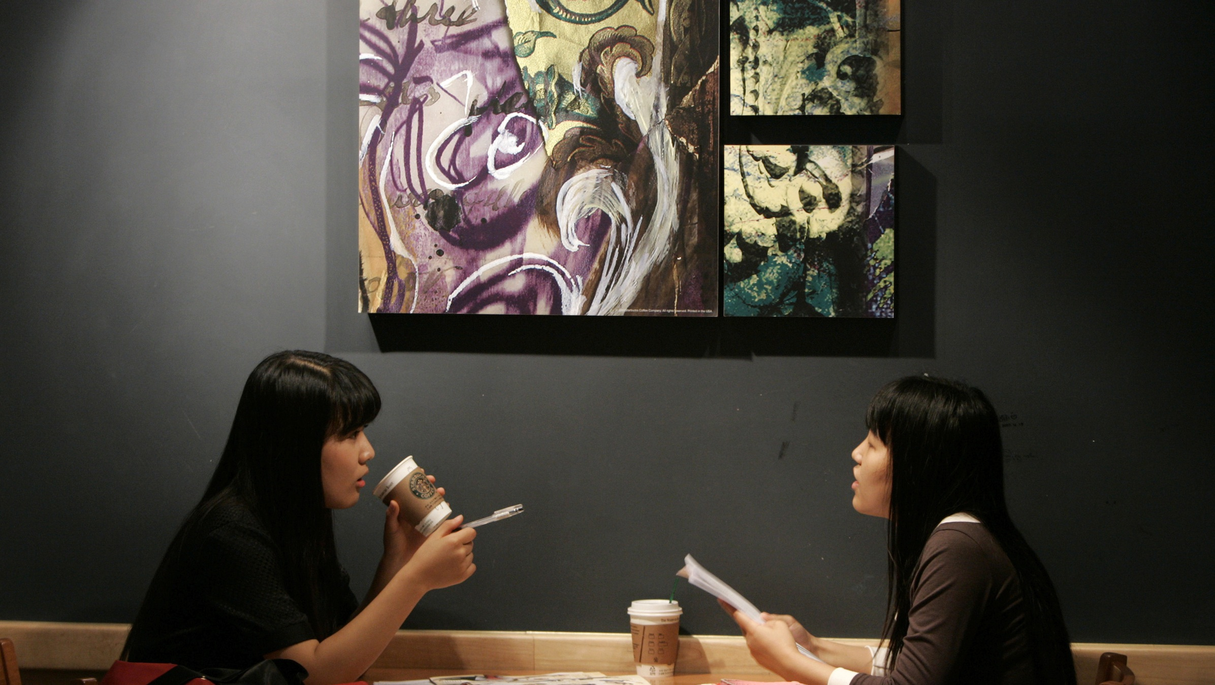 Two women talk as they drink coffee at a Starbucks coffee shop in central Seoul September 21, 2007. Photo taken on September 21, 2007. To match feature ASIA-TEA/    REUTERS/Han Jae-Ho (SOUTH KOREA) - RTR1UXJD