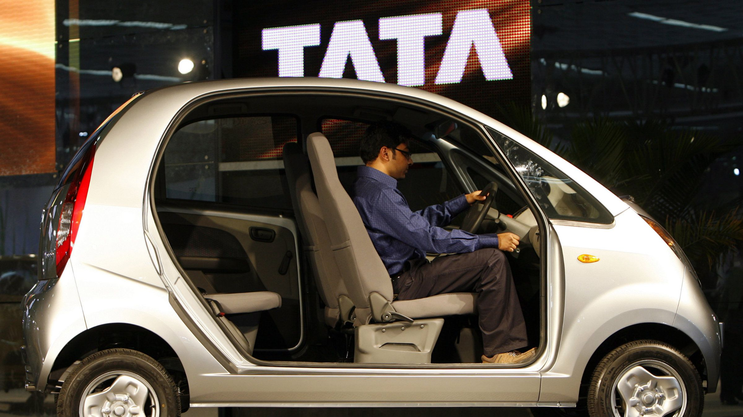 """An onlooker sits inside the Tata Group's newly launched """"Nano"""" car at the 9th Auto Expo in New Delhi January 16, 2008. The chairman of Indian automaker Tata Motors has left open the possibility of bringing the Nano to Europe and hinted at Fiat helping it out with the world's cheapest car."""