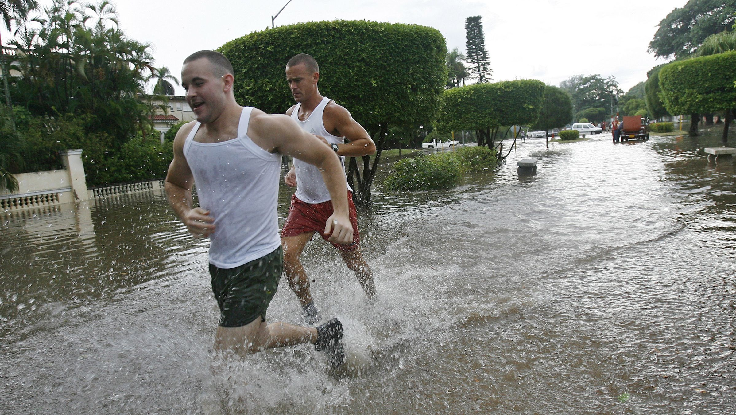 Joggers run through flooded streets after torrential rains hit Havana August 26, 2008. Weather forecasters predicted on Tuesday that Hurricane Gustav would skirt the western coast of Cuba and enter the Gulf of Mexico as a powerful Category 3 hurricane with winds in excess of 100 mph by Sunday. REUTERS/Claudia Daut (CUBA) - RTR21Q33
