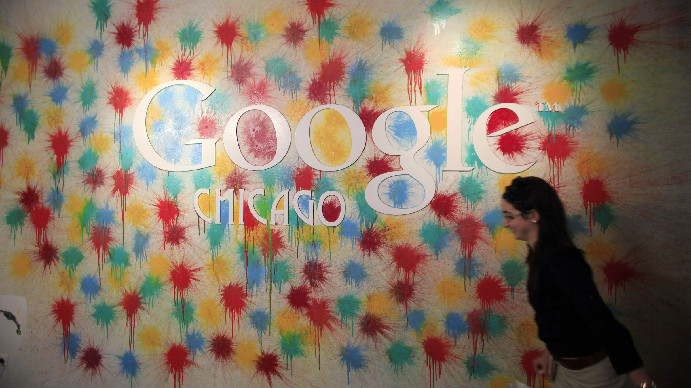A woman walks past the Google Chicago headquarters logo in Chicago, March 20, 2012.