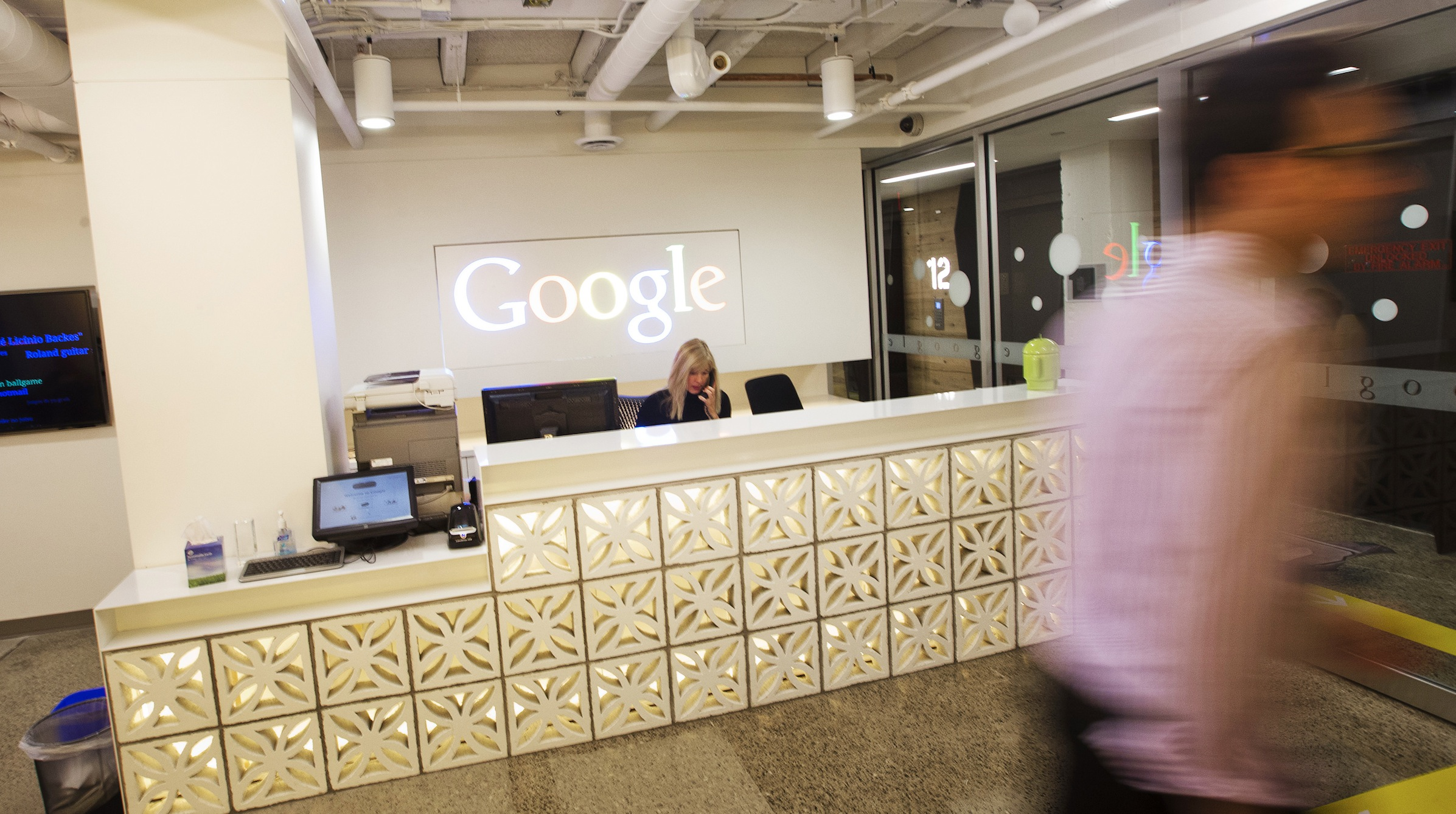 A man walks by the reception desk at the new Google office in Toronto, November 13, 2012.  REUTERS/Mark Blinch (CANADA - Tags: SCIENCE TECHNOLOGY BUSINESS) - RTR3ACWN
