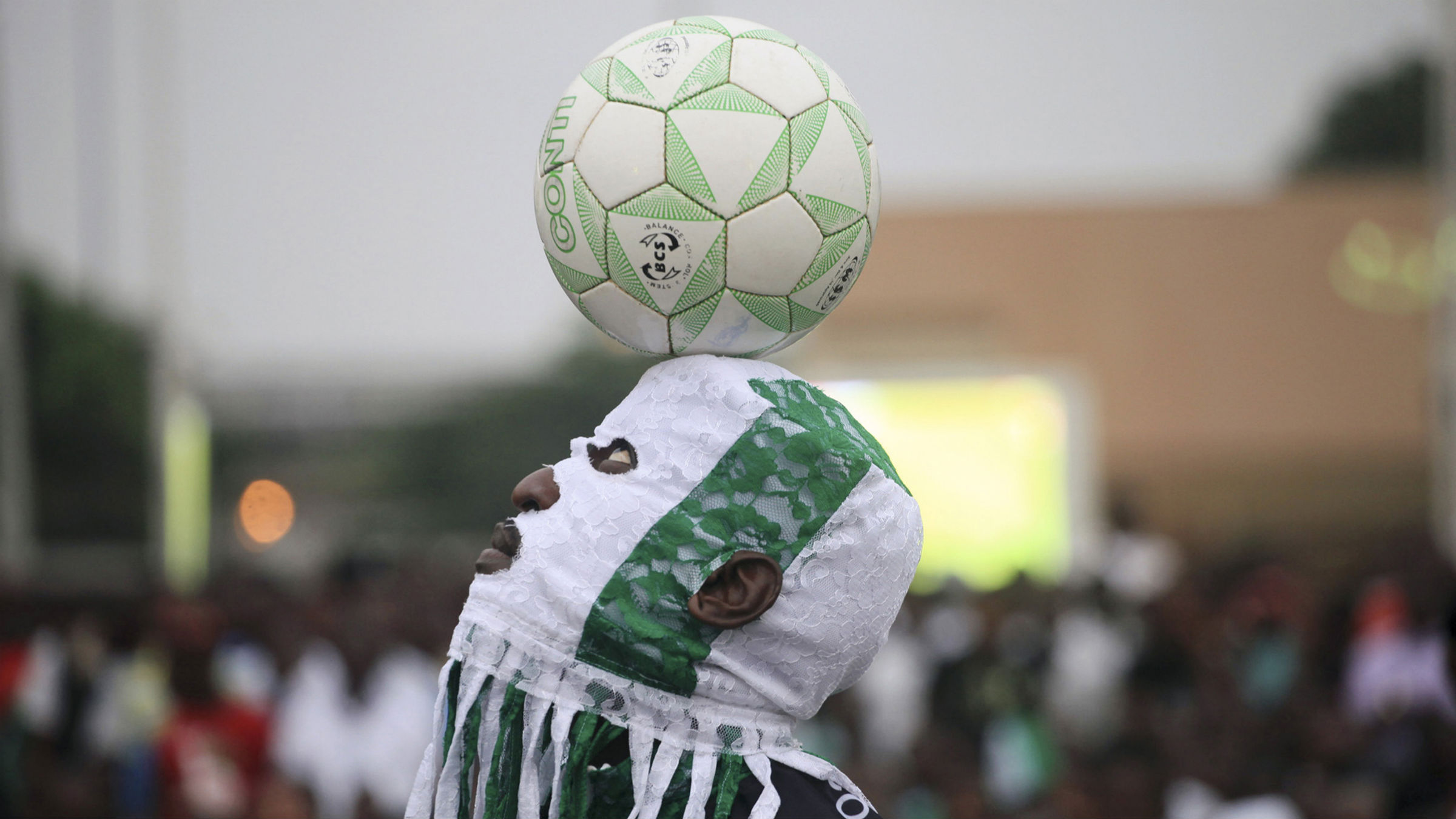 A performer juggles a ball at an open football viewing centre before the start of the match between Nigeria and Burkina Faso during the final match of the Africa cup of Nations at Testlim Balogun stadium in Lagos February 10, 2013.