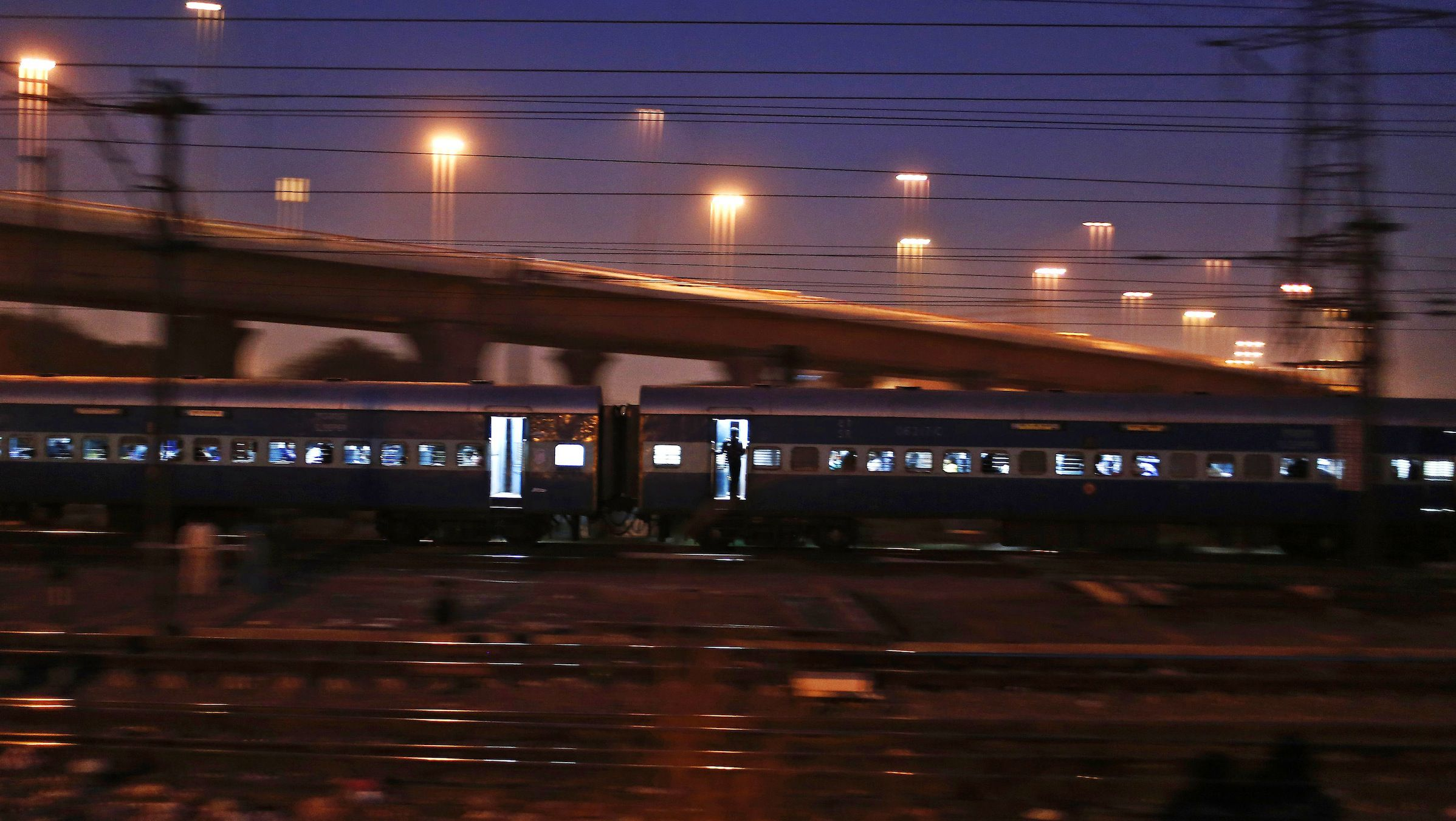 A commuter stands on the doorsteps of a moving train in New Delhi March 6, 2014. REUTERS/Adnan Abidi (INDIA - Tags: SOCIETY TRANSPORT) - RTR3G4LG