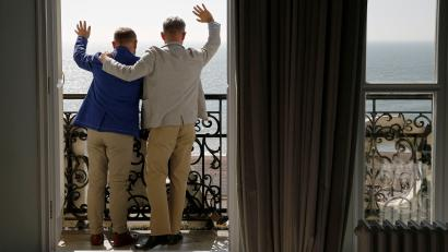 Gay couple Andrew Wale (R) and Neil Allard wave to members of the media from their hotel after marrying in the first same-sex wedding in Brighton, which took place at the Royal Pavilion, in southern England March 29, 2014.