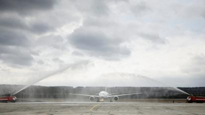 A Lufthansa plane is sprayed by water trucks while waiting to take off.