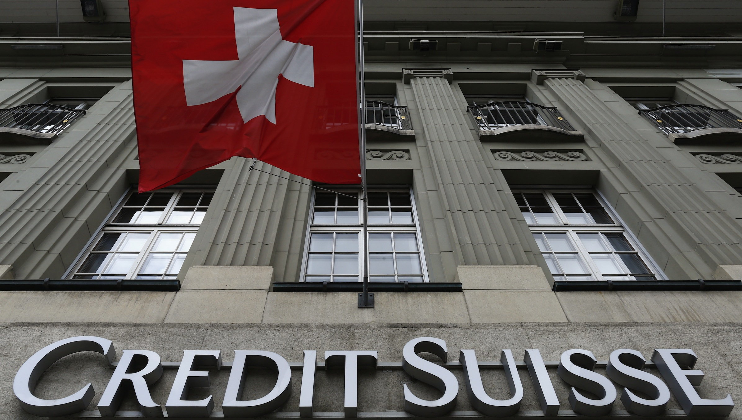 The logo of Swiss bank Credit Suisse is seen below the Swiss flag at a building in the Federal Square in Bern May 15, 2014. REUTERS/Ruben Sprich (SWITZERLAND - Tags: BUSINESS LOGO POLITICS) - RTR3PAPY