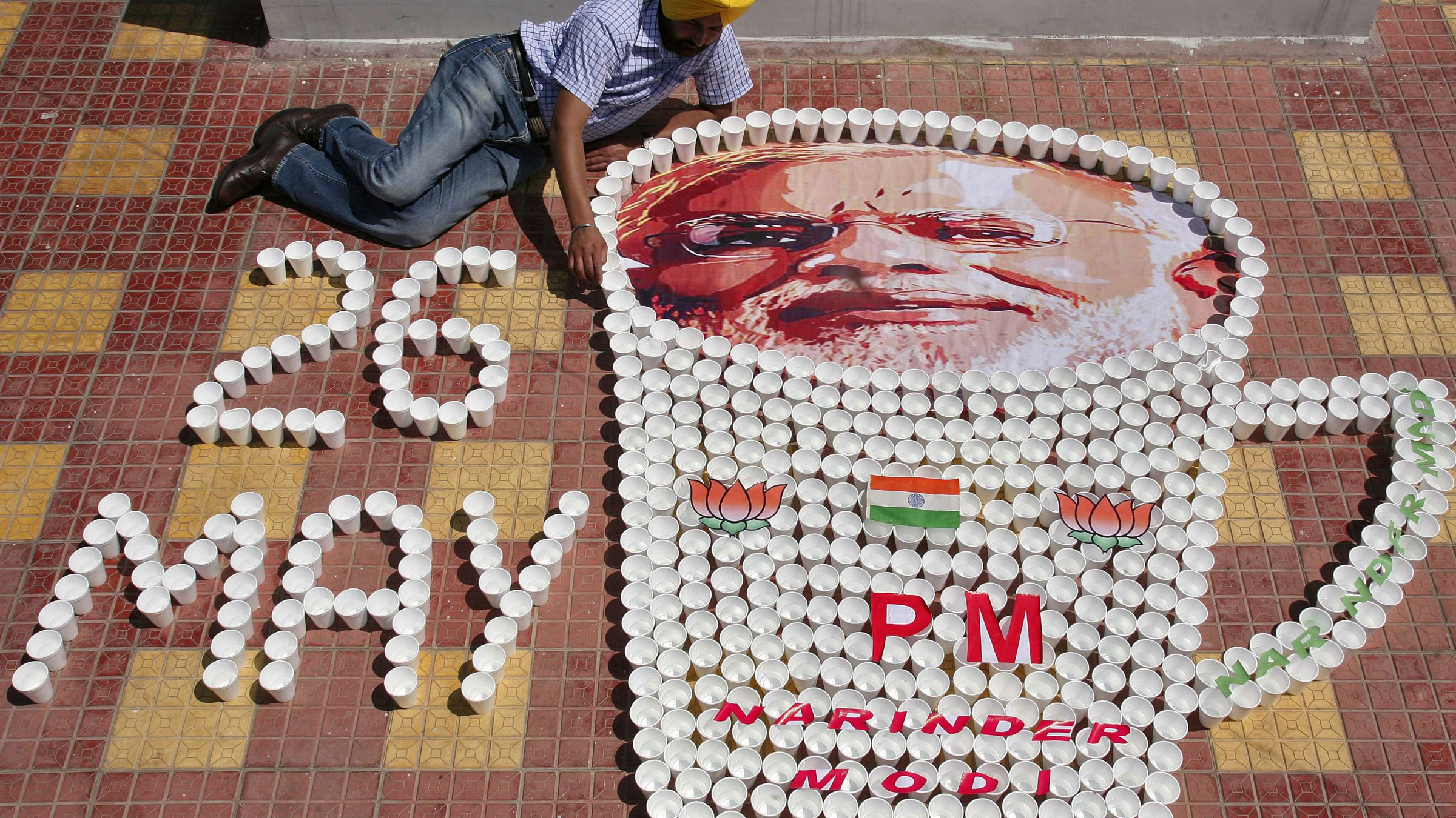 DATE IMPORTED:May 24, 2014Indian artist Harwinder Singh Gill poses with his new creation, an image of Indian Prime Minister-designate Narendra Modi and tea cups ahead of Modi's swearing-in ceremony on Monday, in the northern Indian city of Amritsar May 24, 2014.